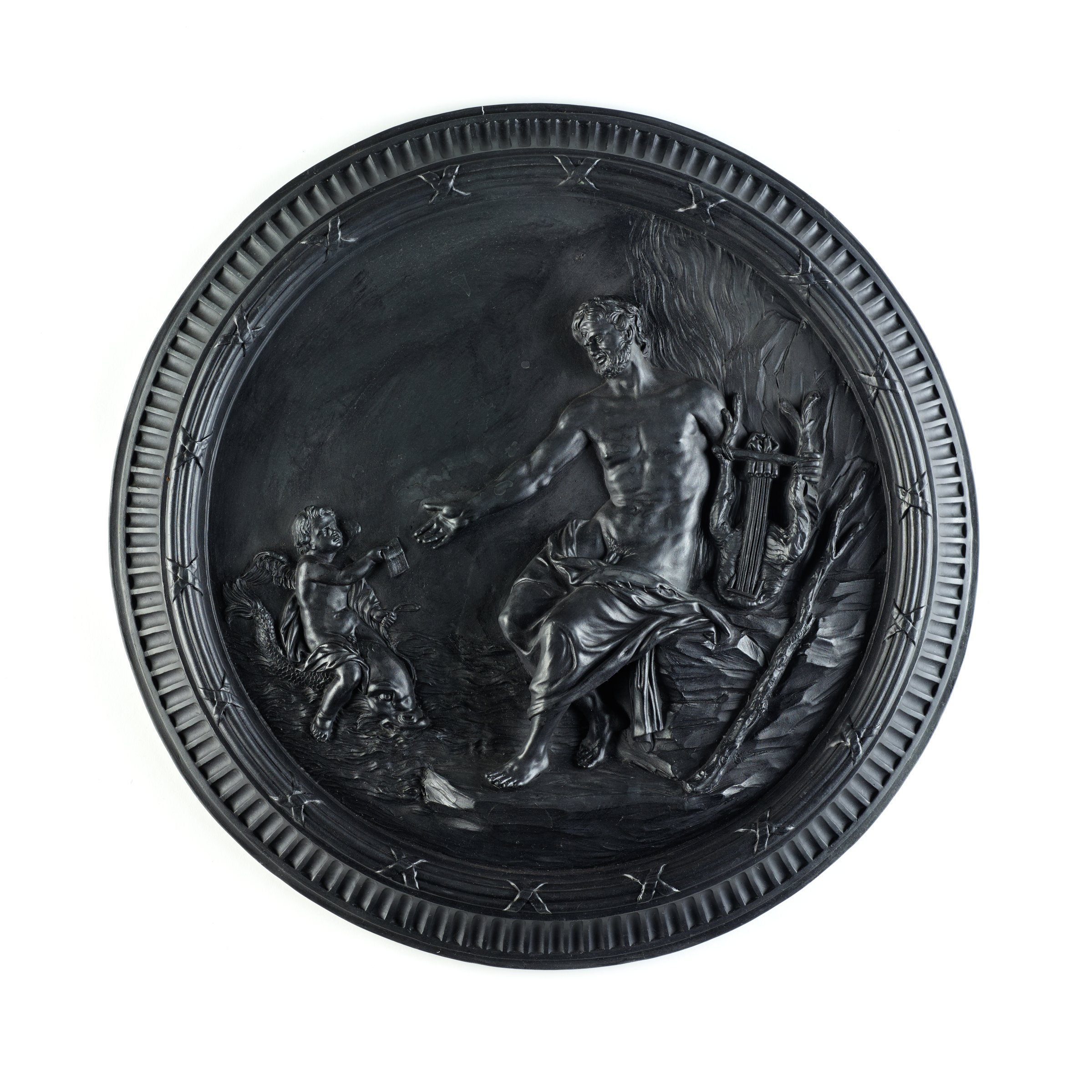 Large, polished round plaque of black basalt, self-framed, the main scene molded in high relief depicting Polyphemus seated on a rock with a lyre reaching his right hand out to Cupid who rides a dolphin and in turn extends his right hand, which holds a letter, to Polyphemus.