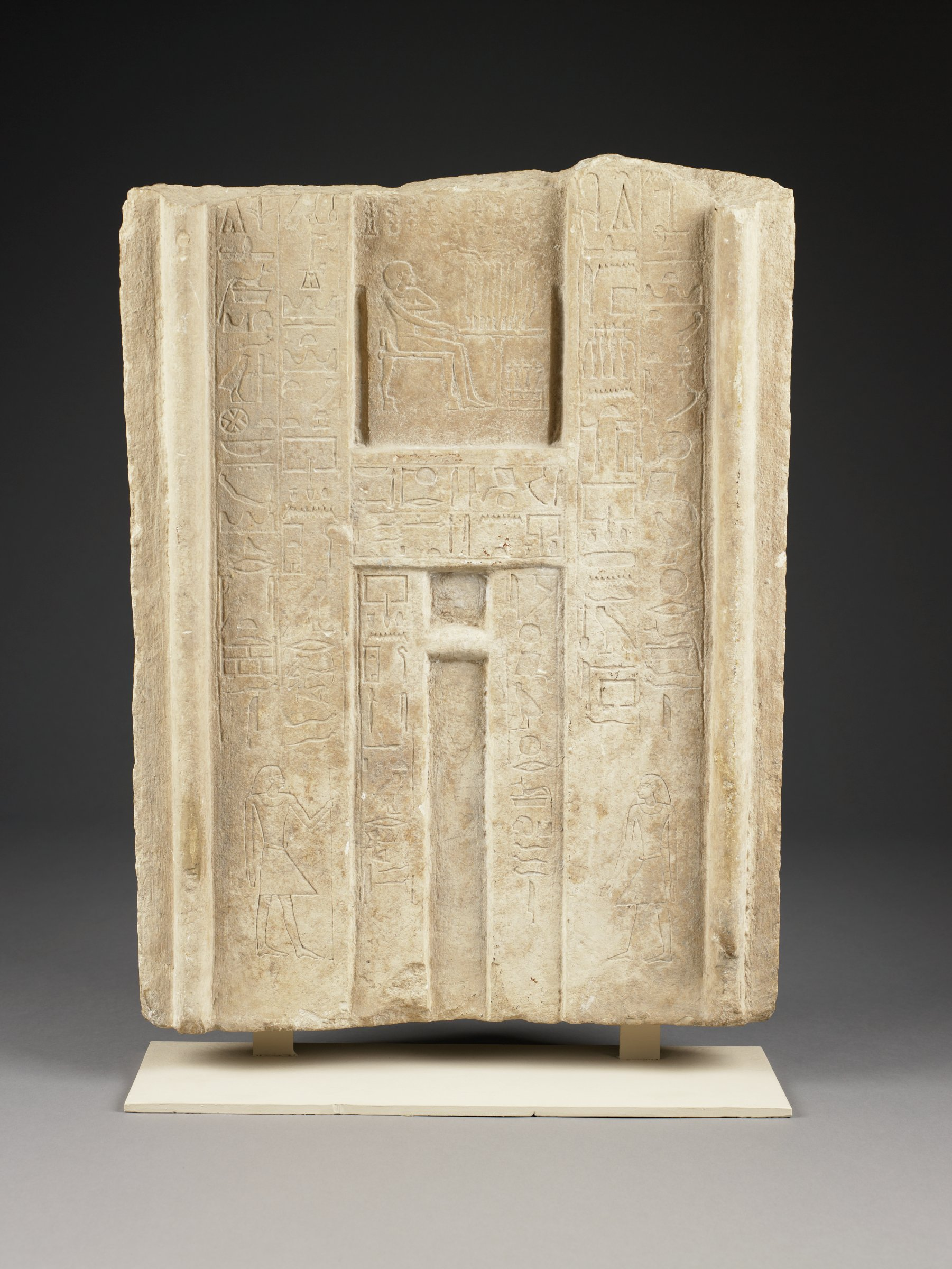 Limestone slab with relief carving representing a doorway; also hieroglyphic inscriptions and image of man identified as General Fefi seated before a table.