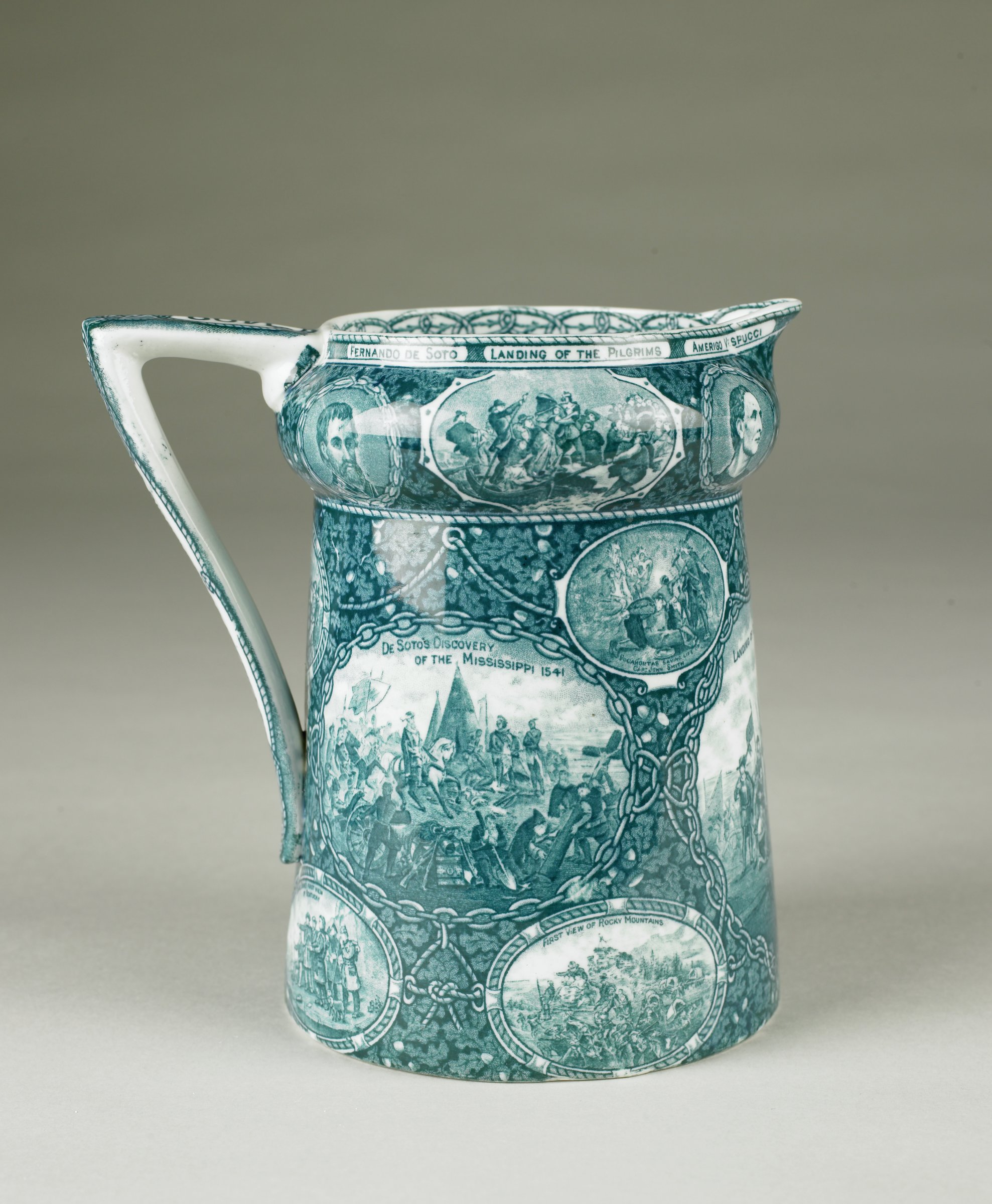 """Pitcher commemorating the """"Discovery of America"""" of transfer-printed, lead-glazed earthenware in shades of monochrome blue-green, of tapering form with a bulbous neck, the shaped handle inscribed """"1492"""" and """"Discovery of America,"""" the body decorated with oval reserves depicting many firsts in American history, including three large oval reserves enclosed by chains depicting """"William Penn's Treaty with the Indians 1683""""; """"Landing of Columbus""""; and """"De Soto's Discovery of the Mississippi 1541,"""" below these are four smaller reserves enclosed by ropes depicting """"Landing of Roger Williams""""; """"Columbus before Ferdinand and Isabella""""; """"Daniel Boone's first view of Kentucky""""; and """"First view of the Rocky Mountains,"""" and above the large reserves are two small reserves with scrolled borders depicting """"Pocahontas saving the life of Capt. John Smith"""" and """"Landing at Jamestown,"""" under the handle is one reserve enclosed by rope depicting """"Pilgrims receiving Massasoit,"""" on the bulbous neck are additional reserves with the portrait of """"Du Quesne""""; """"Fremont raising the flag""""; """"Christopher Columbus""""; """"Fernando de Soto""""; """"Landing of the Pilgrims""""; and """"Amerigo Vespucci,"""" all against an oak leaf ground with ropes, anchors and a ship's porthole, with small spout, the inside lip of the pitcher with a pattern of entwined ropes."""