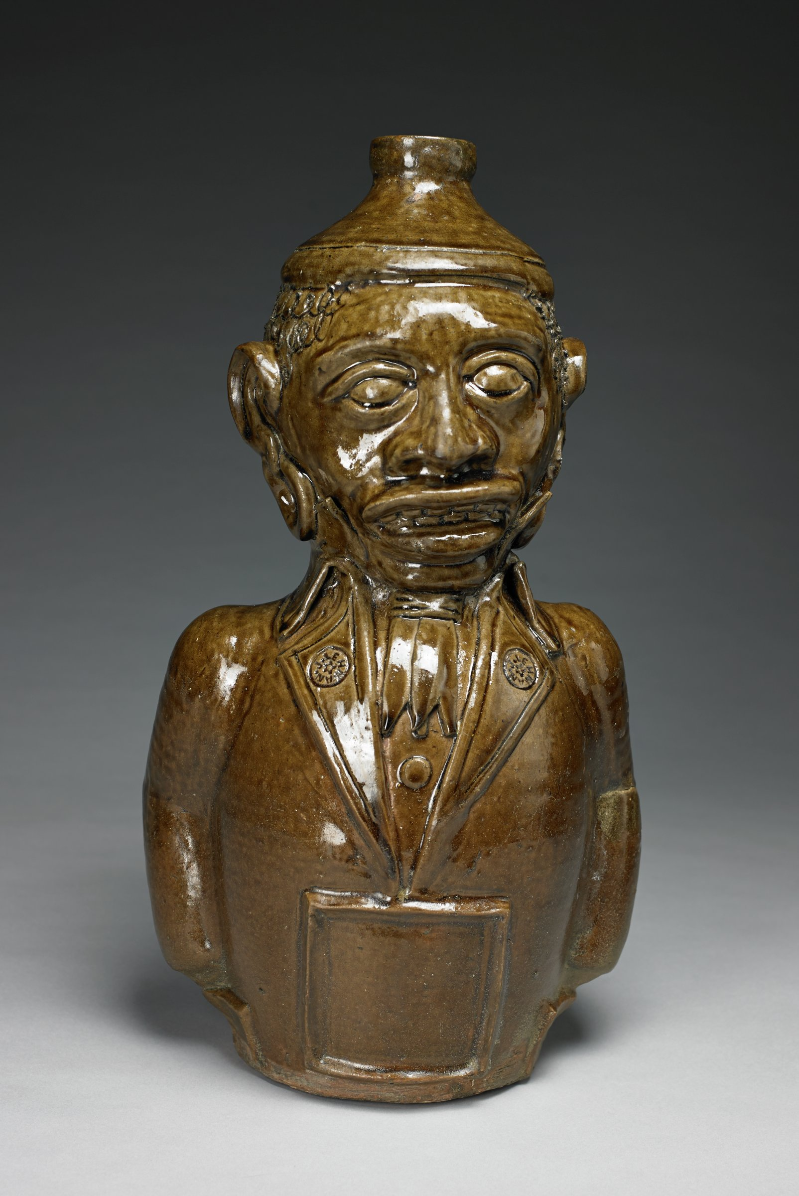 """A figural jug depicting an African-American man with exaggerated facial features, particularly his caricatured lips, nose and ears. His curly hair is formed by incised repeating loops, resembling scribbles. He wears a cap, hoop earrings, shirt with a stand up collar (and single visible stud or button), cravat, and a coat with broad lapels and buttons impressed with """"J. LEHMAN,"""" the maker's name. A large, buckle-like square probably surrounded a paper label for whatever product the jug contained. The figure has arms, but no hands, and is rendered to appear as if his hands are shoved in the pockets of his coat. There are small air holes at the back of each arm to prevent an explosion during firing. The jug's handle is a shaped like the number 9, and is finished (where the tail of the handle meets the body of the jug) with a mold-formed grape and grape leaf motif found in some of Lehman's other decorated vessels. There appears to be an oval incised on the bottom of the vessel."""