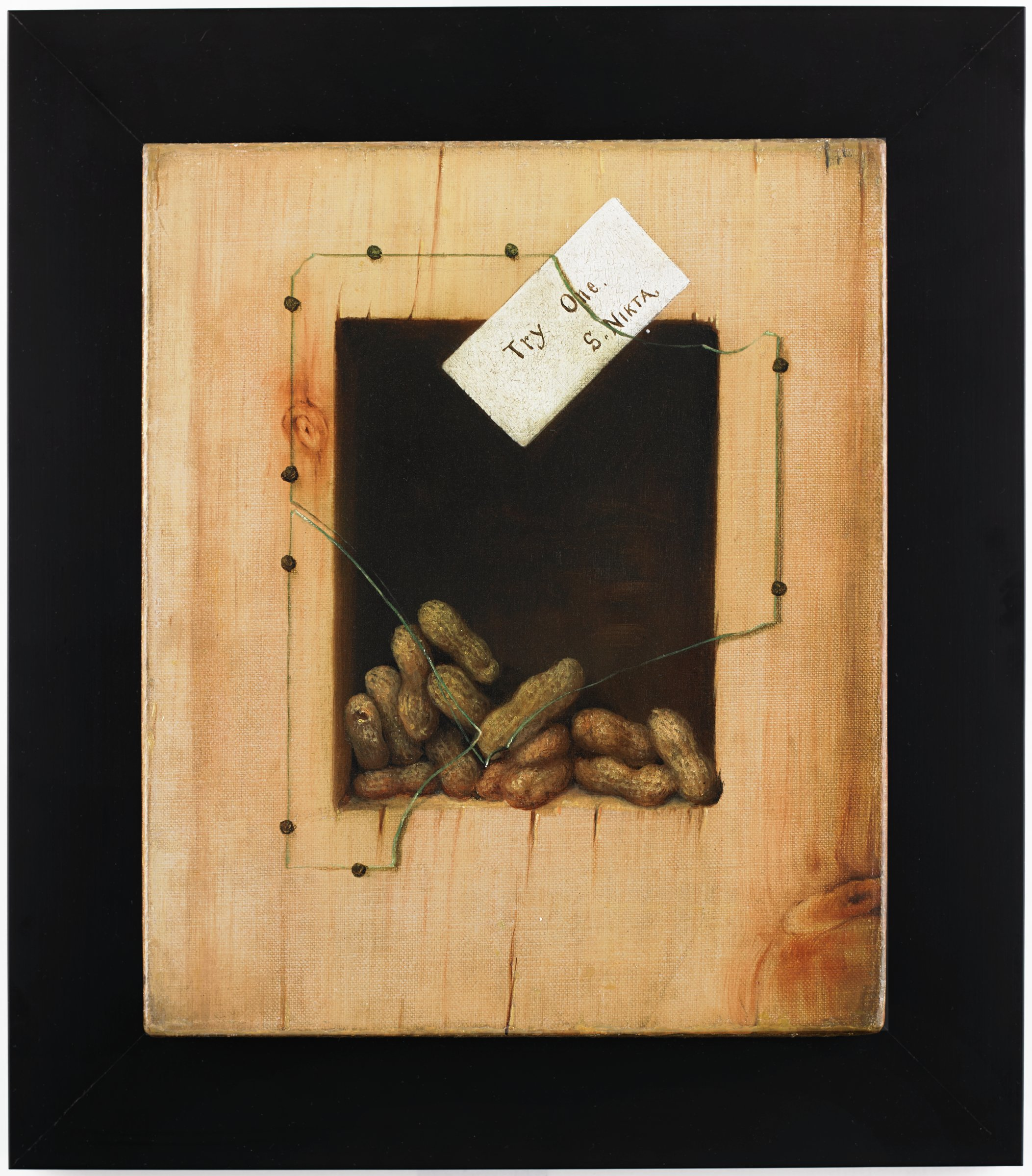"""A trompe-l'œil (French, """"trick the eye"""") still life painting consisting of a stretched canvas, painted around all four sides to resemble a rectangular piece of wood cut from a longer plank. The top and bottom edges have a series of lines painted with a thick impasto to resemble the radial grain of a cut board. At the center of the composition is a dark hollow recess covered with a broken pane of glass held in place by nine tack nails, which contains 14 peanuts, functioning as a makeshift peanut dispenser. Tucked behind the pane of glass at the top of the recess is a white paper card which reads """"Try One. / S. NIKTA."""" """"S. NIKTA"""" is """"Atkins"""" spelled backwards, probably the name of a friend or patron of the artist."""