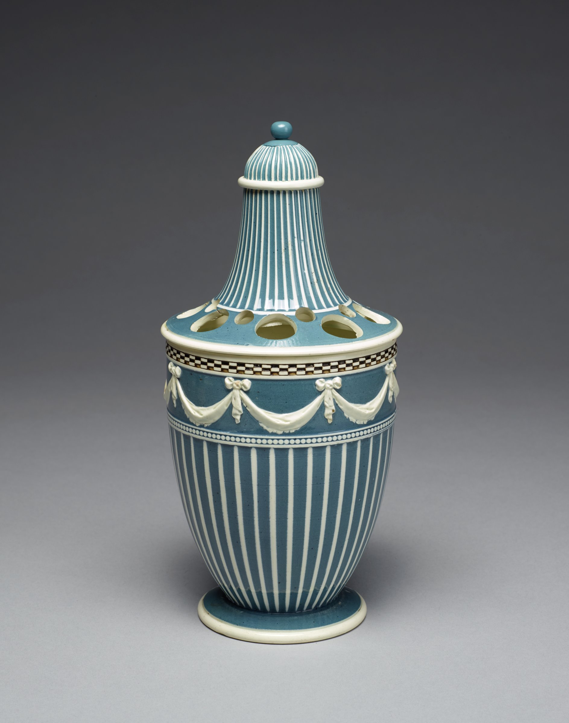 Tall, bottle-shaped potpourri vase, of white stoneware covered with a blue glaze and a clear pearl glaze, the main body with a pattern of blue and white stripes below a blue band with molded white swags hanging from ribbons, below this a band of beading and above a band of checkerboard pattern, with two covers, one with flat shoulder and pierced with eight large and eight smaller holes, with long striped neck, the other a small, domed, stripped cover with ball finial is a facsimile.