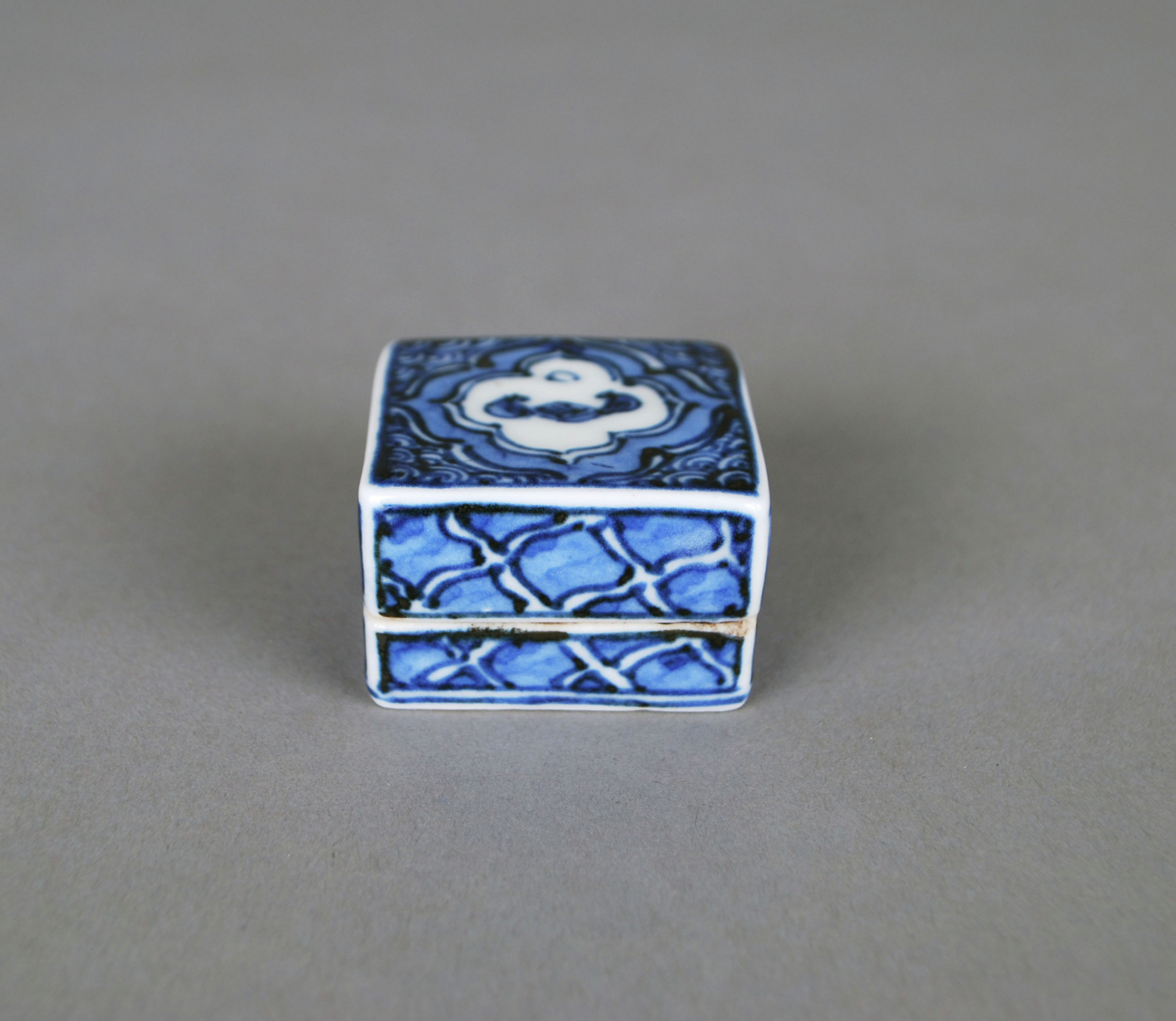 A small, lidded box decorated in blue and white with a bat under the moon and lozenge patterns on the sides.Cube-Shaped Incense Box (Kogo) Painted in Cobalt Blue with Go-Playing under a Moon Motif