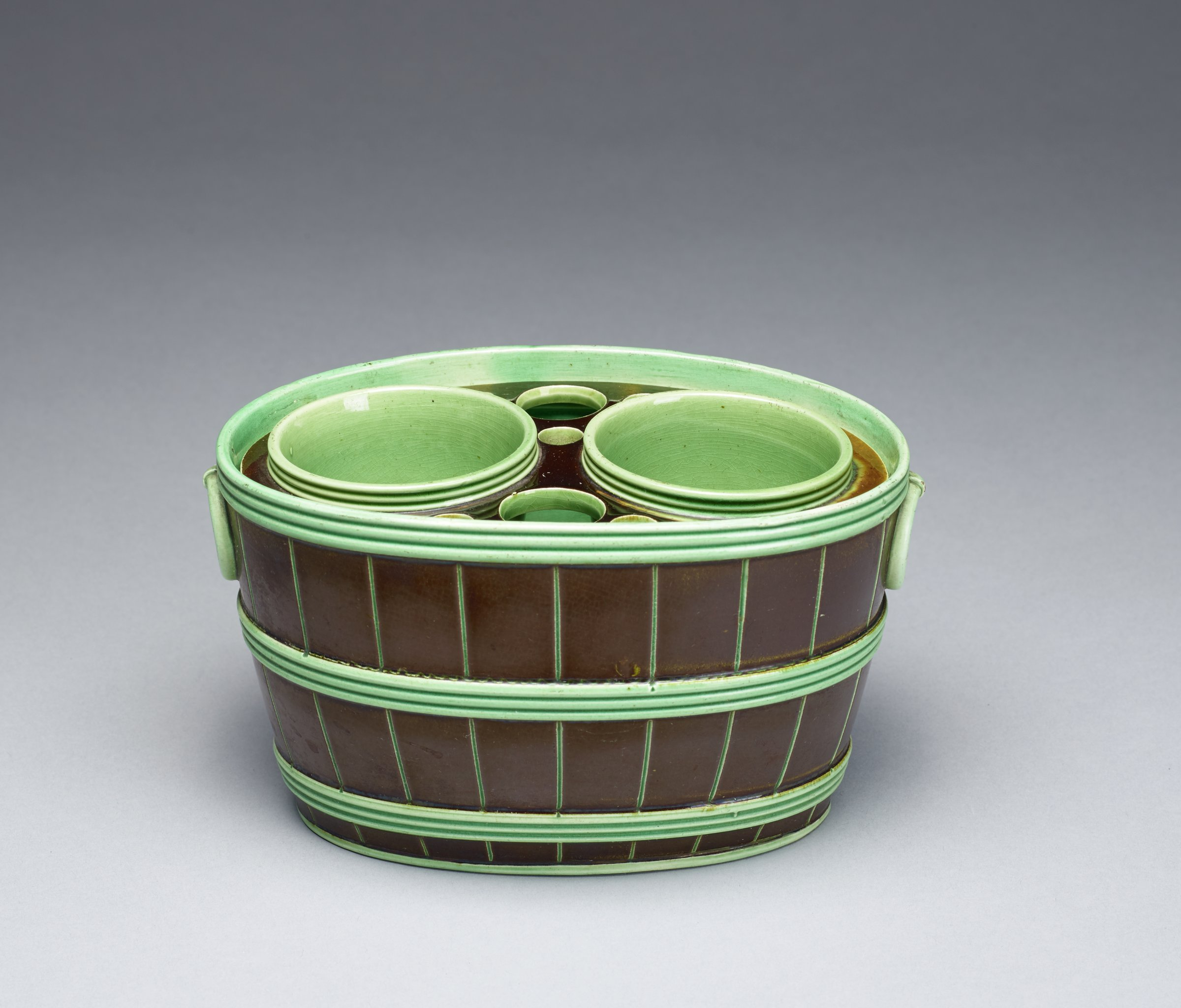 Bulb pot in the form of an oval barrel, the body glazed black with bands of green, the removable fitment with two spouts to accommodate bulbs and with two larger and five smaller air holes in the fitment, the interior and the underside are glazed green, the topside of the fitment is covered with a tortoiseshell glaze.