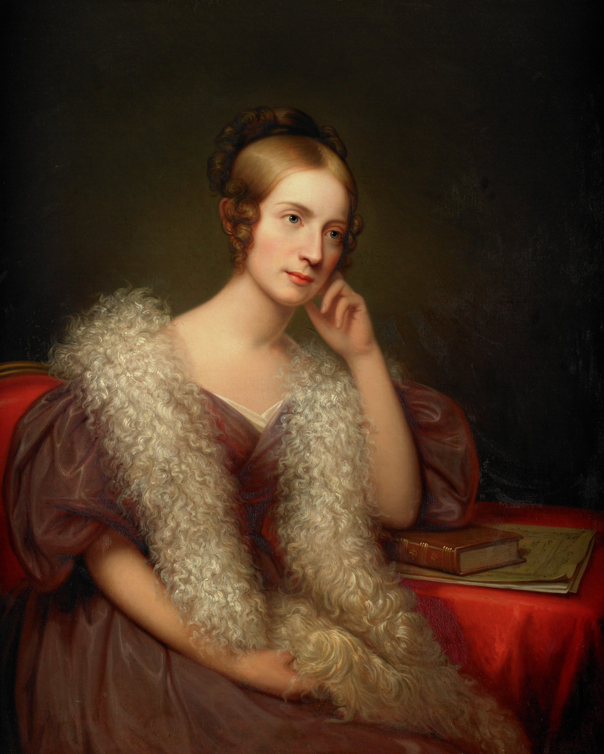 Swan-necked woman in a purple dress with a fur collar sitting pensively; her left arm rests on a book, atop of table decked with a red cloth