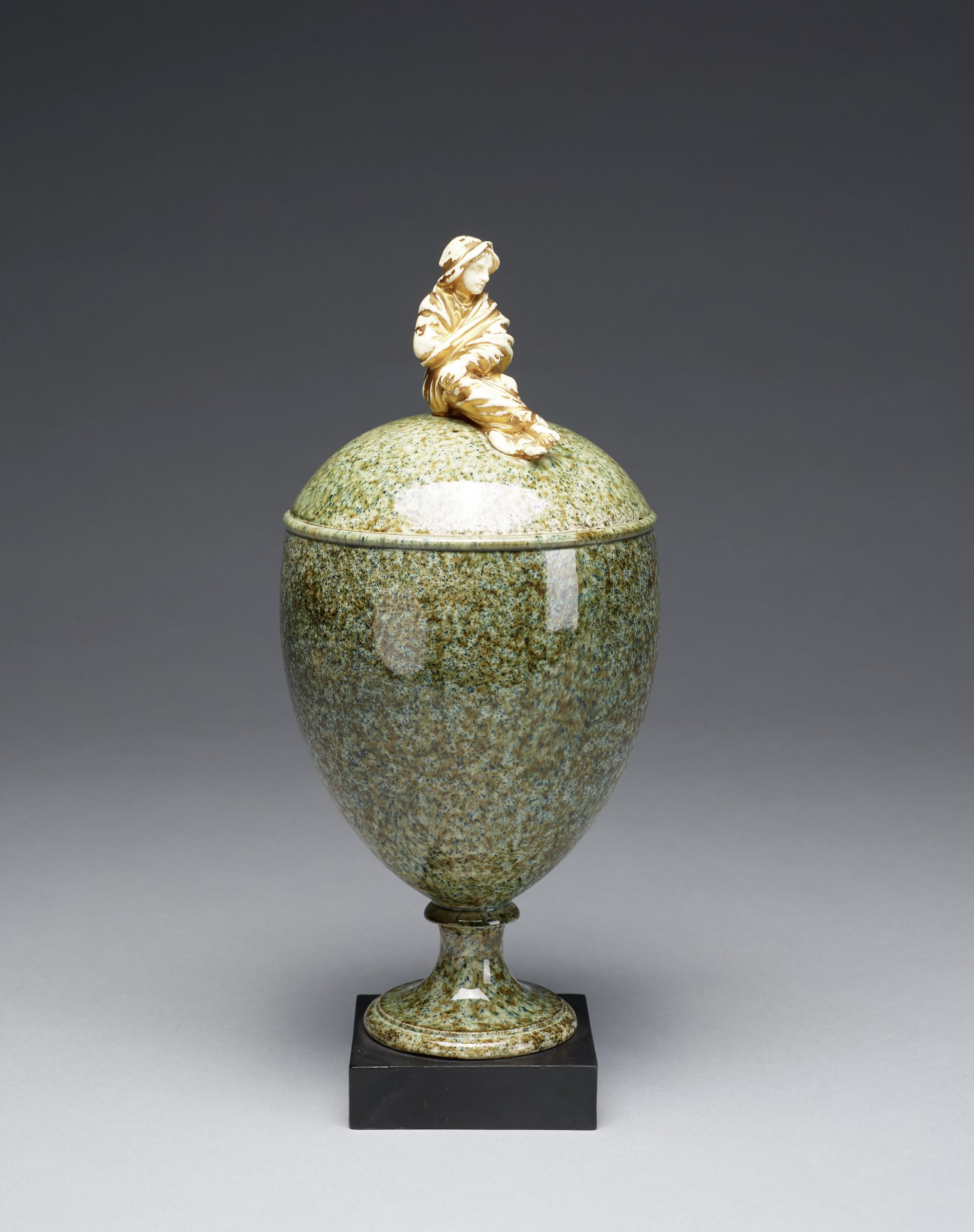 """Covered oviform footed vase of creamware covered with variegated green glaze in imitation of granite, with gilt """"Sibyl"""" finial in the form of a draped, seated female figure, with right leg crossed over left and left hand resting on right knee, the vase mounted on small, square basalt base"""