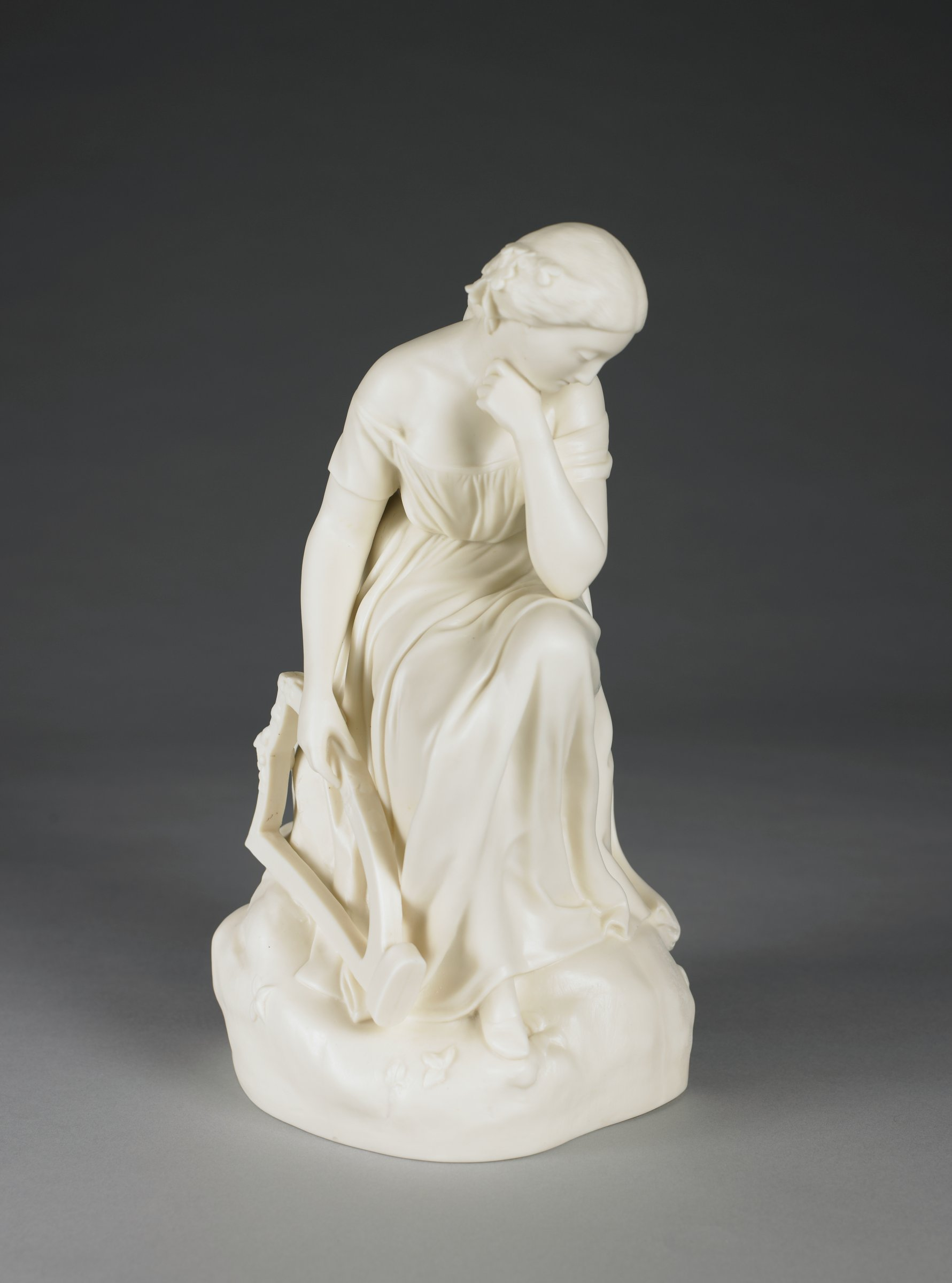 Hollow Parian figure of a seated woman wearing an off-the-shoulder, flowing gown, her left leg propped on a rock, her left arm bent and resting on her knee, her hand at her chin, her right arm dropped and holding a small harp at her side, on an irregular rocky base.