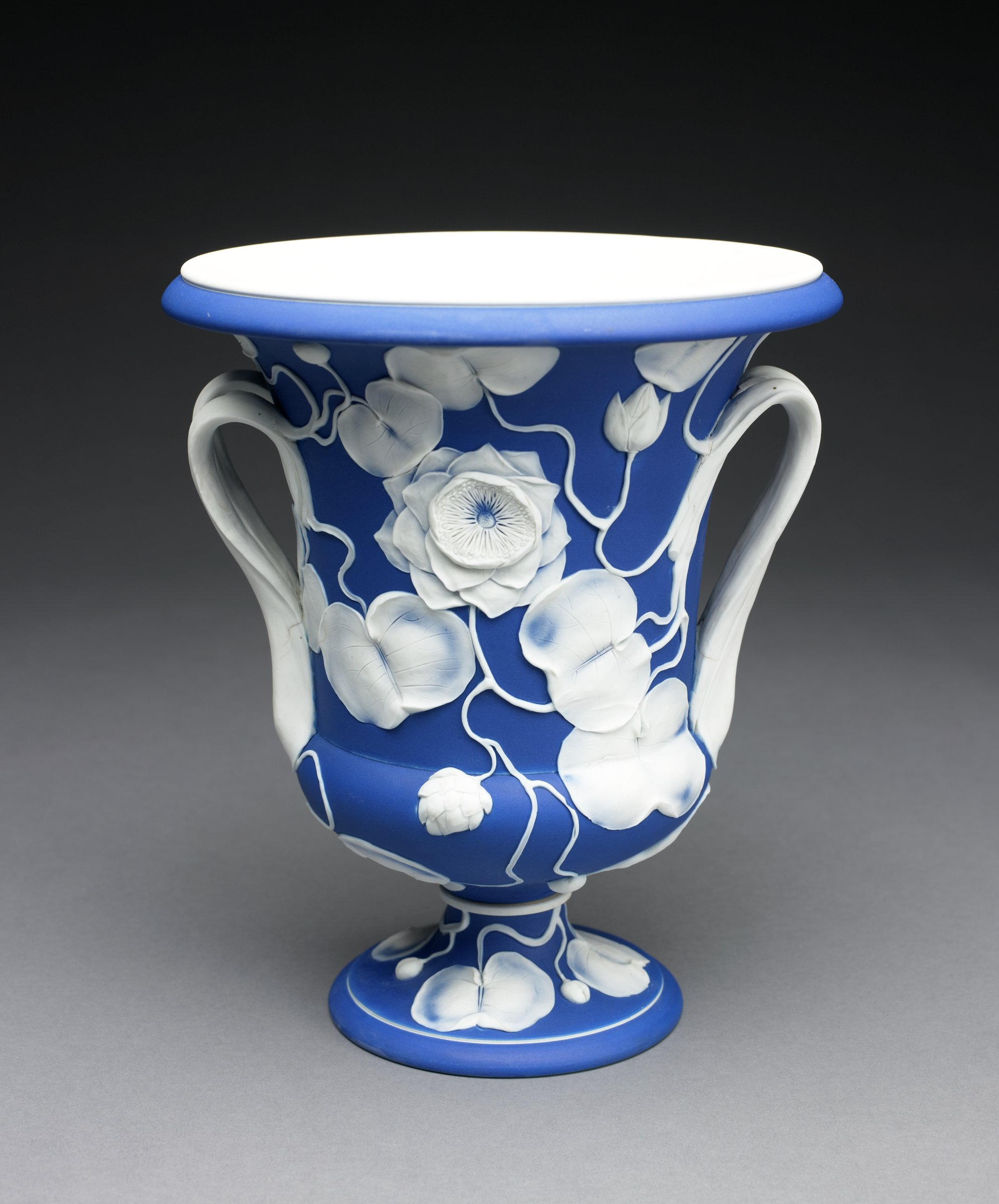 Large white jasper wine cooler with dark blue jasper dip and white relief decoration, urn shaped with two, thick elongated ear-shaped handles that extend from the lower body and loop up and around to become leafy vines, with round foot and flared lip, the body and foot decorated all-over with water lily motifs, leafy elements, flowers and buds, highlighted with shading, the interior white.