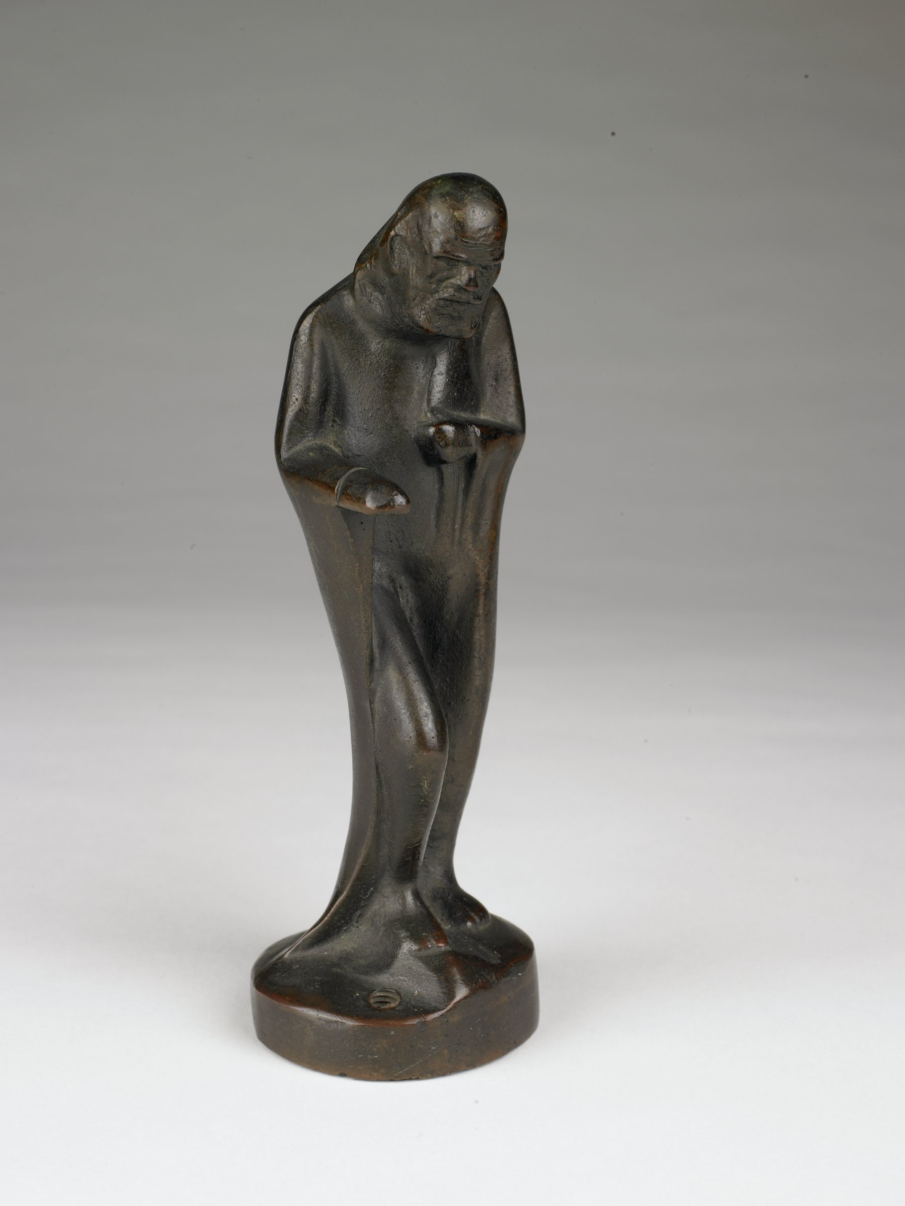 Statuette of a robed, bearded man, monkish in appearance, holding a glass mercury thermometer [missing] as walking stick in right hand.