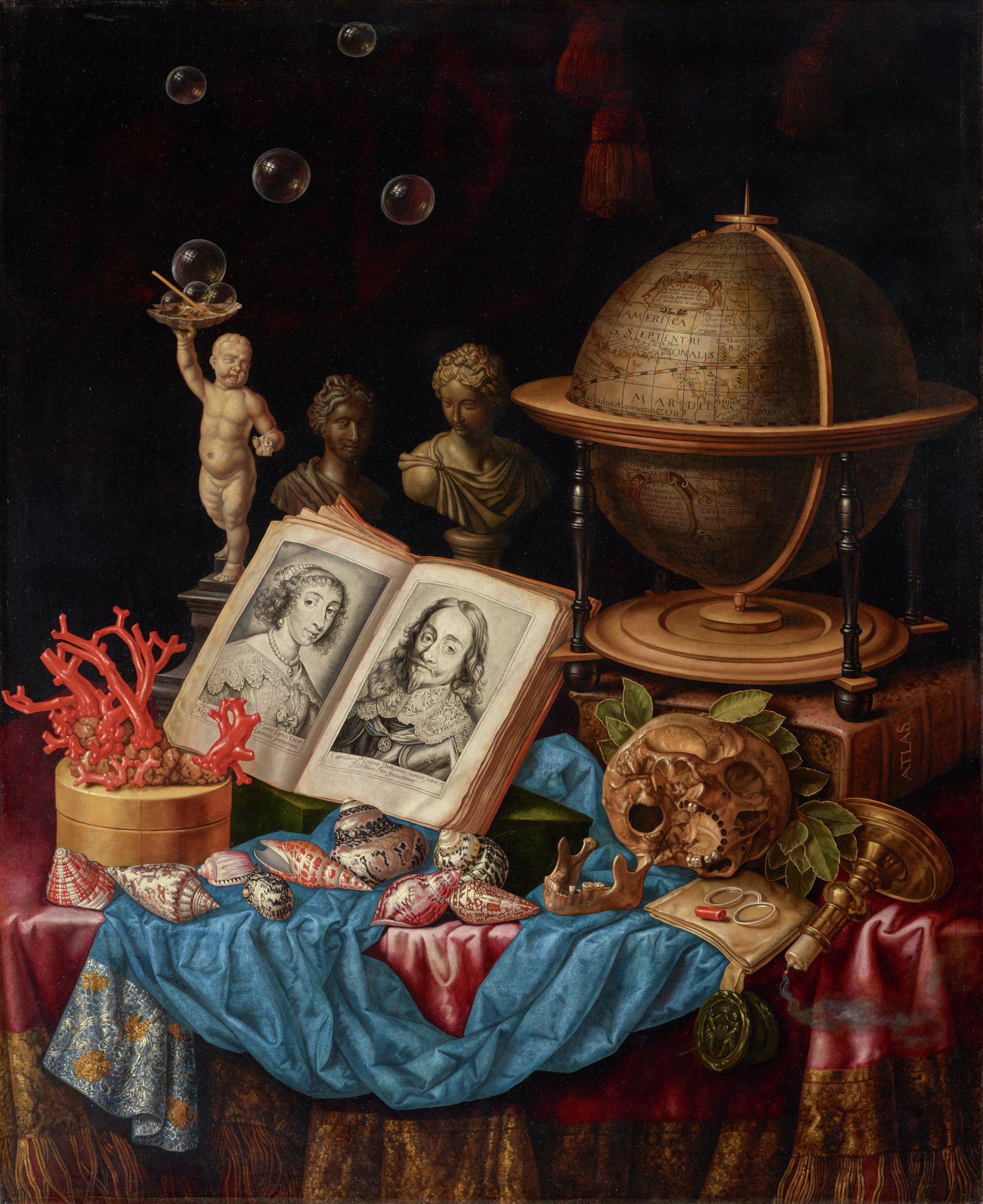 This still life of inanimate objects has been assembled on a table draped with red and blue textiles. The arrangement includes a globe, a skull with a detached jawbone, a book opened to pages with printed portraits of Charles I and Henrietta a round box with coral branches on the lid, shells, a statue of a putto, two female busts, bubbles, glasses, and a candleholder that has fallen over with the candle just snuffed out.
