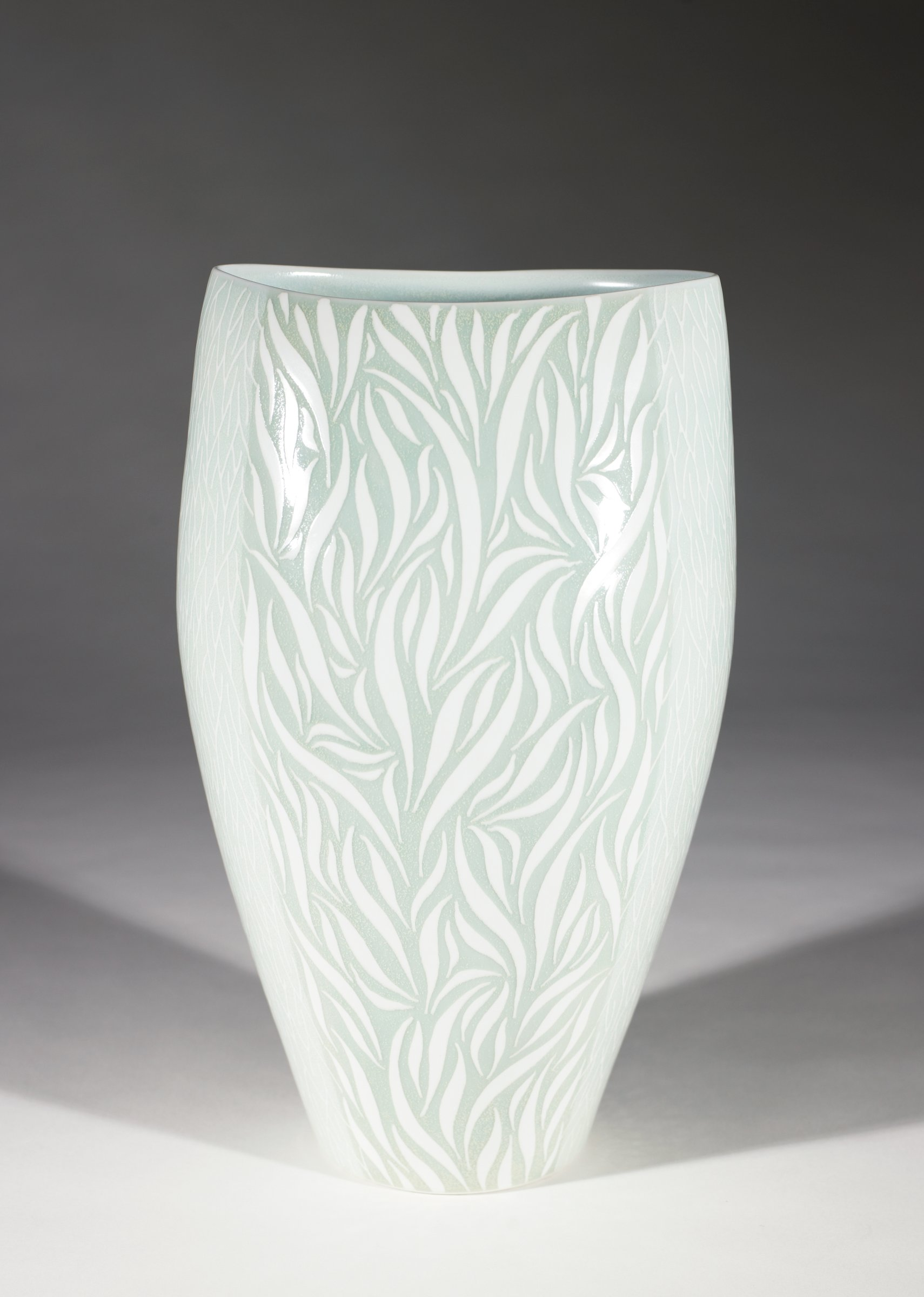 Large, heavy porcelain vase of semi-ovoid form, covered with a celadon glaze both inside and out, the body divided into sections and inlaid in white in a design in two sections of larger twig motifs and in the other two of smaller twig motifs.