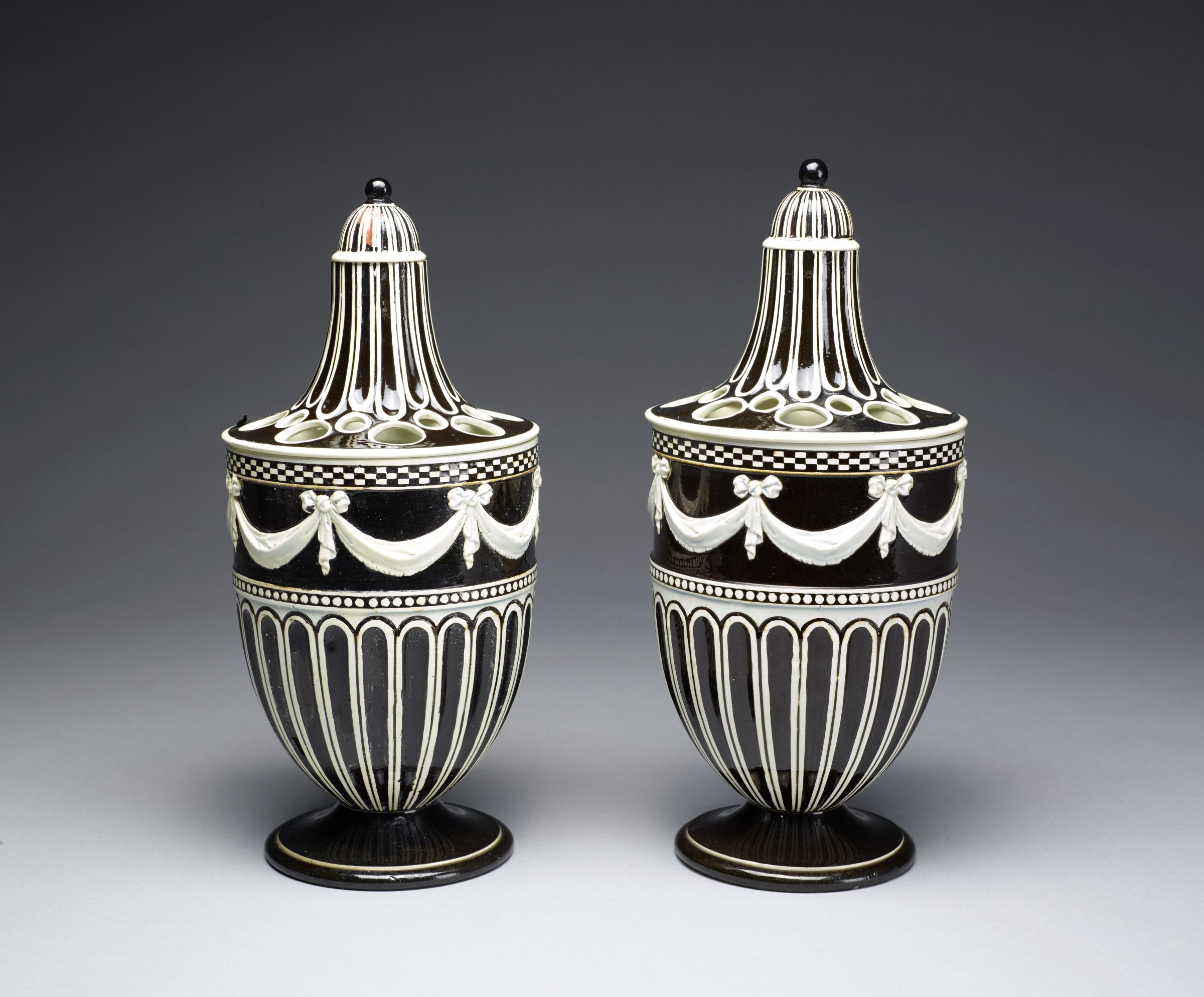 Pair of urn-shaped potpourri vases on round foot, of white stoneware covered with a black glaze under a clear pearl glaze, the lower bodies with gadrooning below a band of beading, with a band of white swags held by ribbons below a checkerboard pattern at the shoulder, the covers with a series of large and small holes and an elongated neck that has similar gadrooning, the domed cover with ball finial.