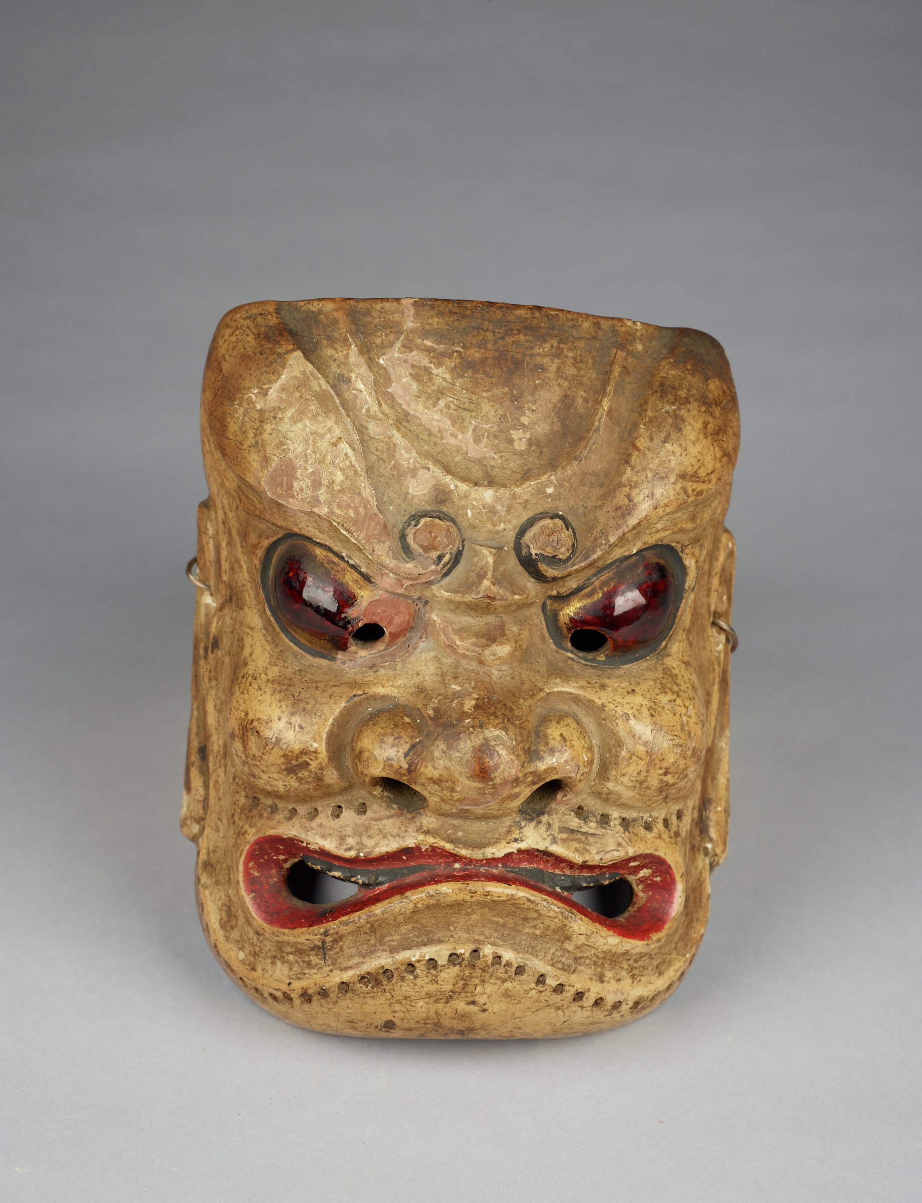 A scowling, frowning face. Lacquered eyes and holes along jaw and upper lip for bristles for beard.