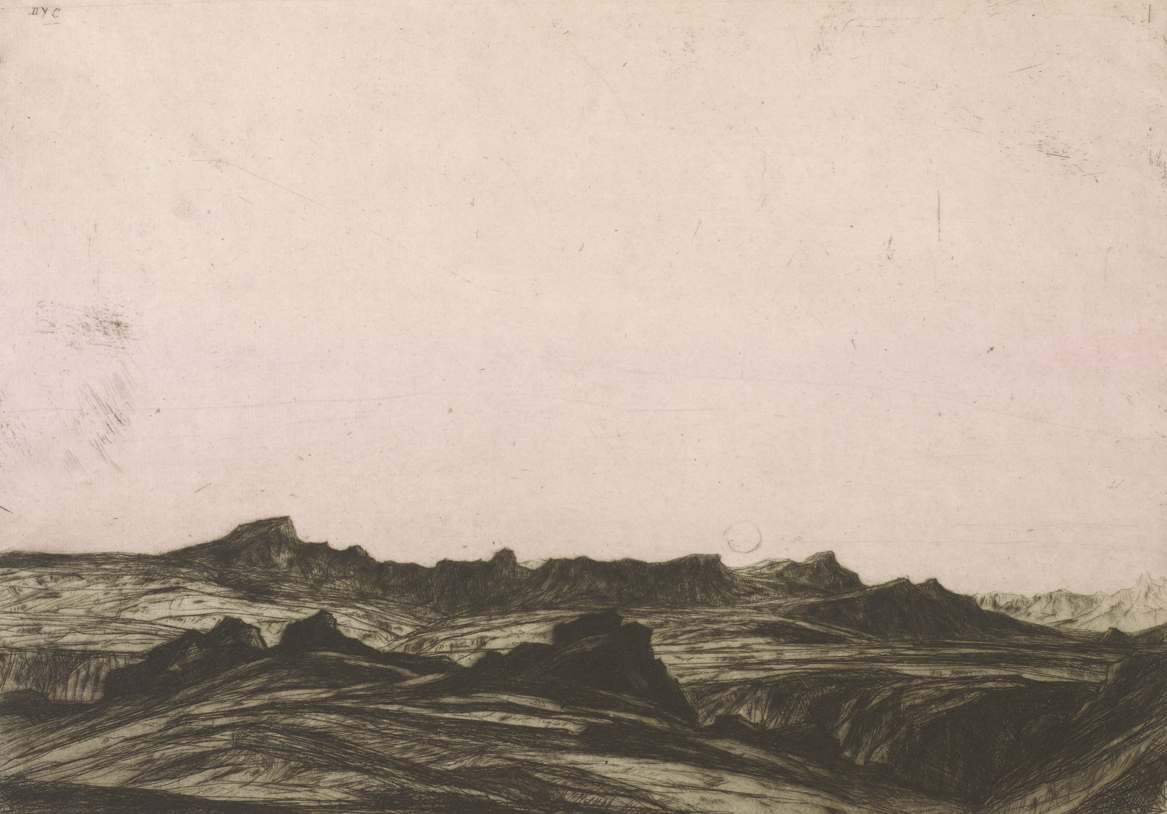 Image of a low horizon with a landscape of jagged mountains. The sun or moon is seen rising from behind the mountains.