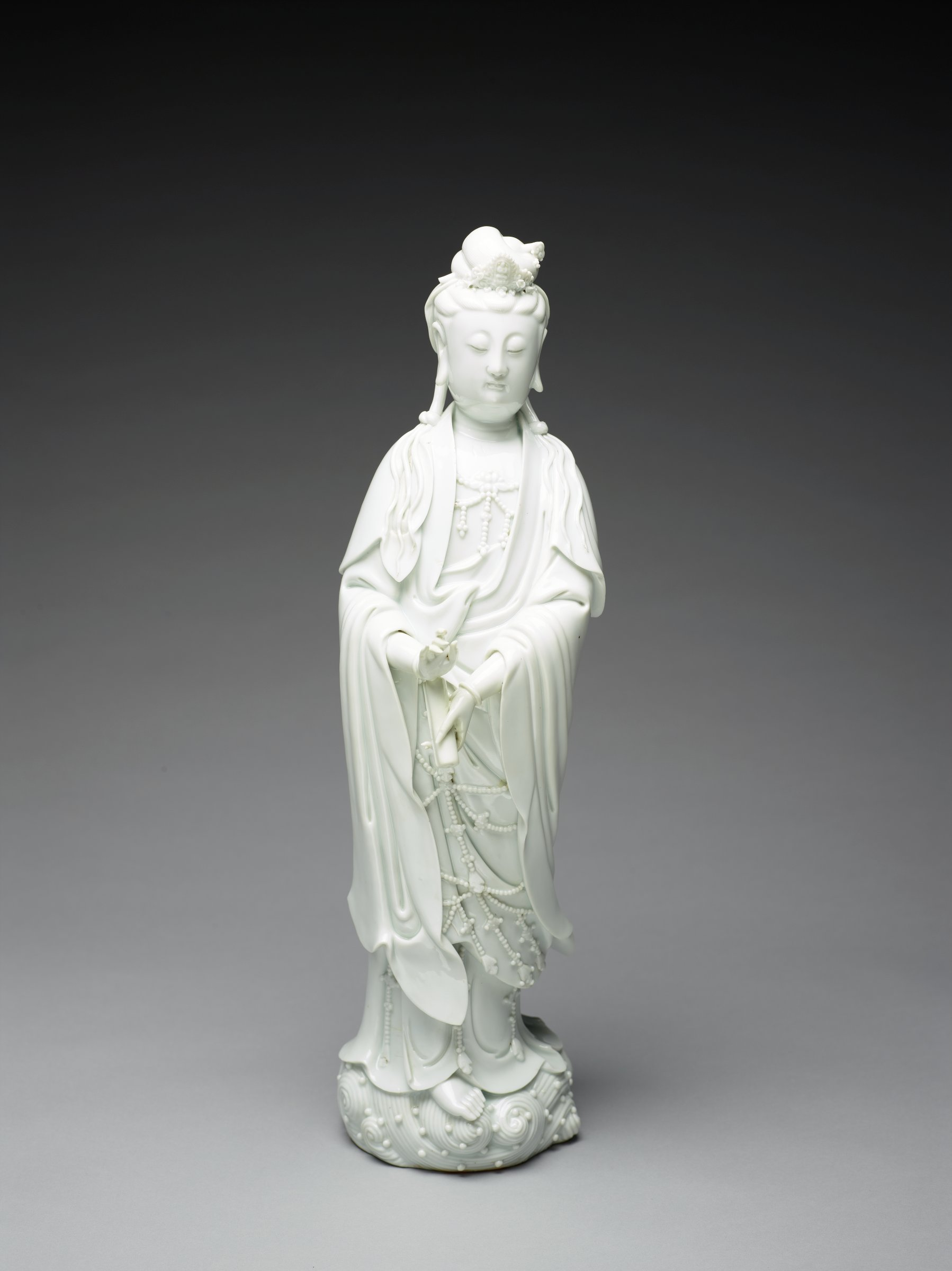 Delicate standing figure of Guanyin on waves. She holds a scroll and has heavy jewelry down her front.