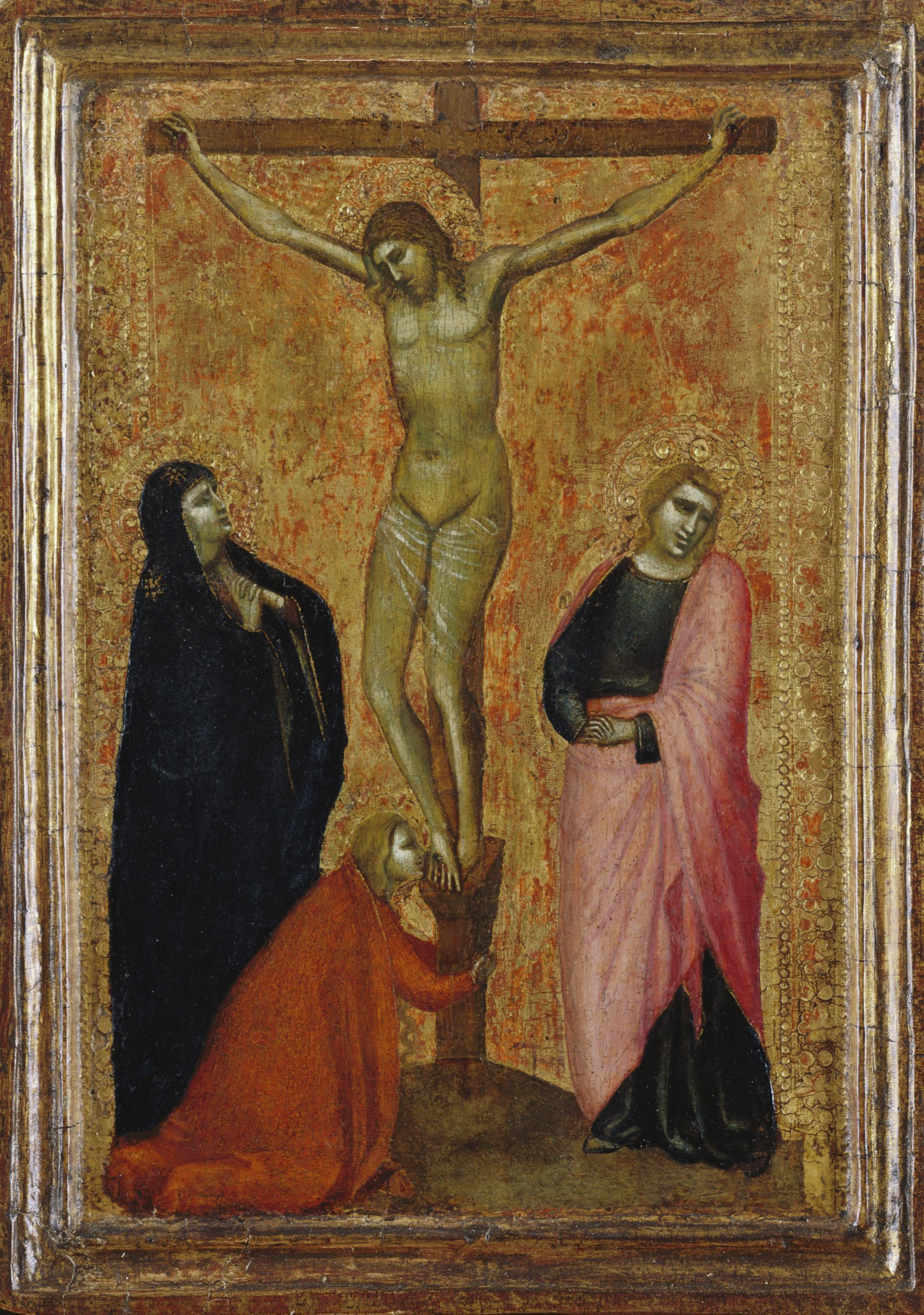 In the center of the panel, Christ is shown crucified on the cross. Mary Magdalene kneels at his feet and kisses them. His mother Mary mourns on the left and St. John the Evangelist on the right.