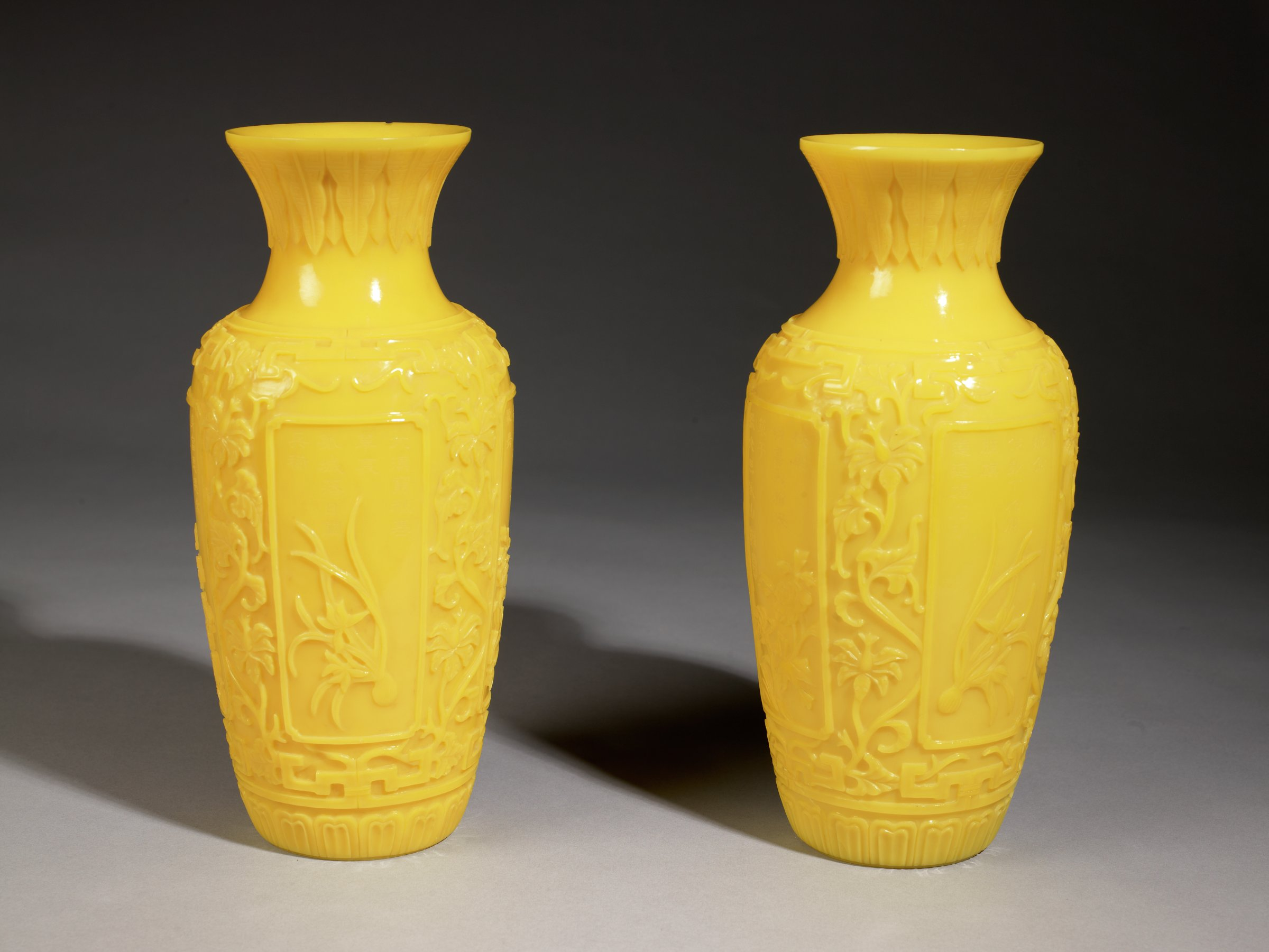 Yellow Peking glass vasesPair of Yellow Glass Vases with Banana Leaf, Daffodil and Orchid Motifs in geometric key with lotus-petal base