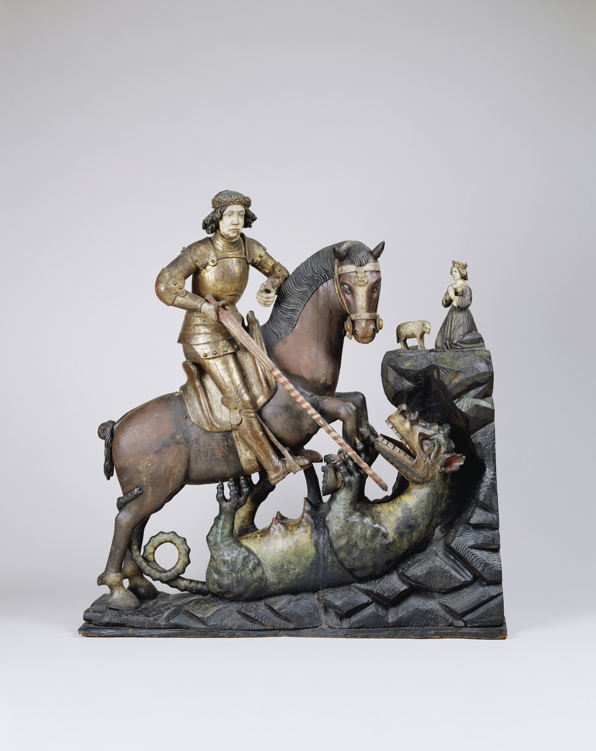 Saint George is riding a horse. The dragon is on its back under the horse. Saint George stabs the dragon with a long sword.