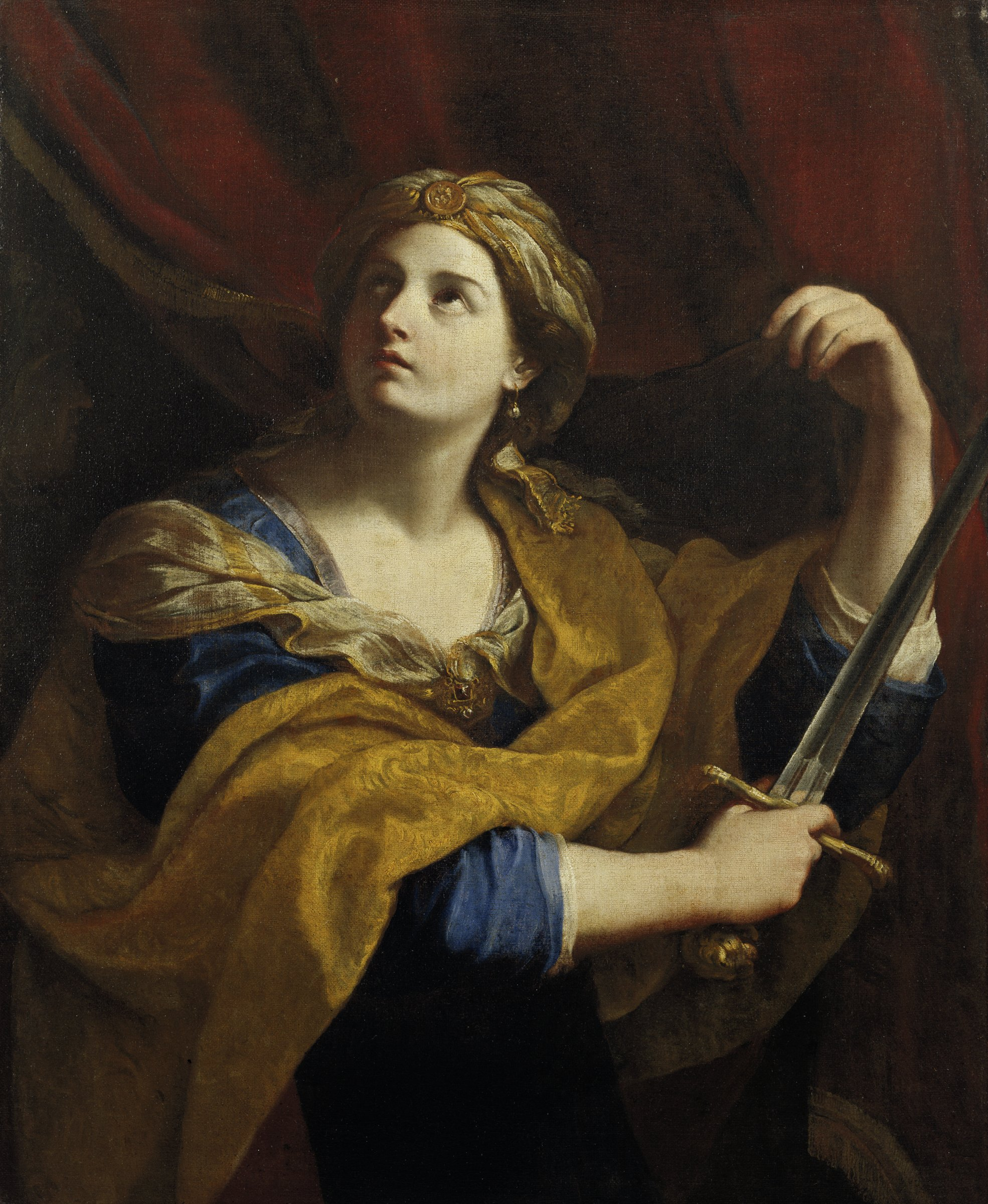 In a darkened tent, a woman looks toward the heavens as she lifts the blade of a sword.