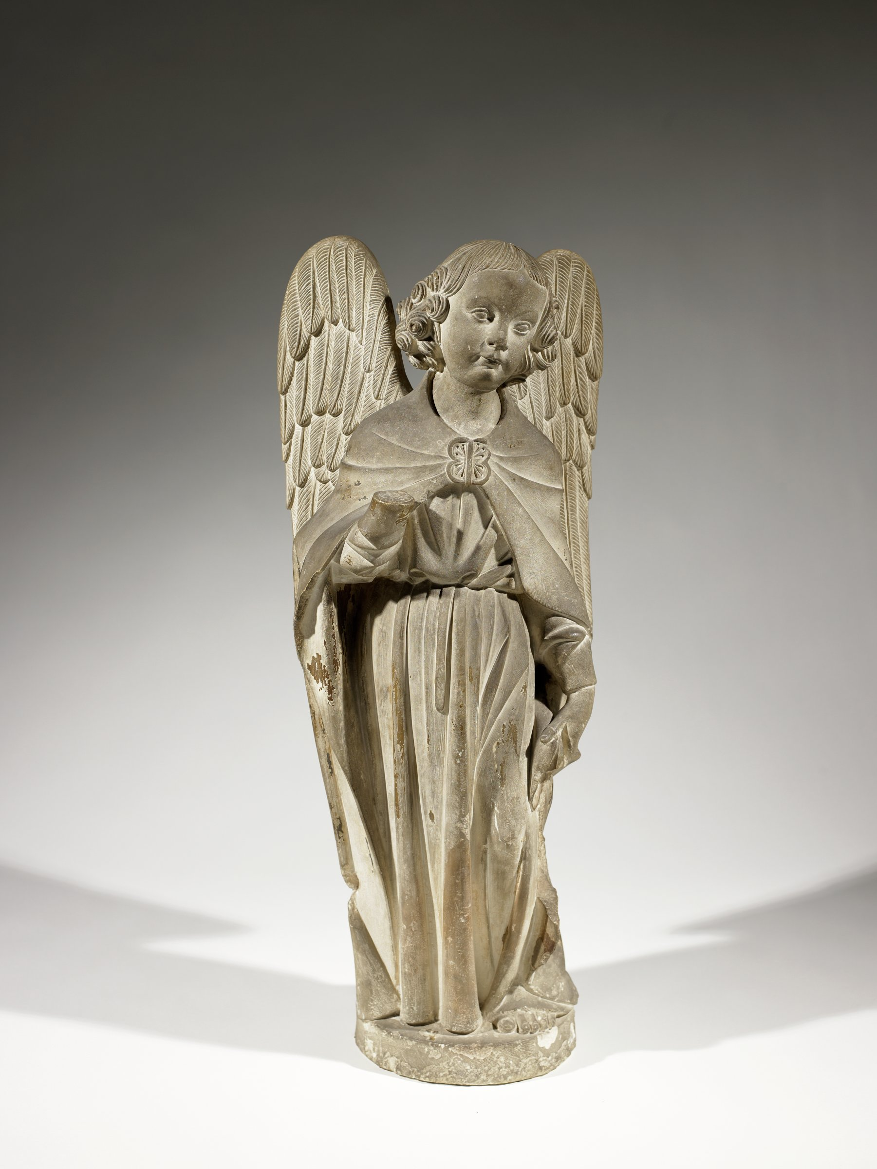 The winged angel is dressed in long robes, standing, and gesturing with its right arm, the hand of which is now missing.
