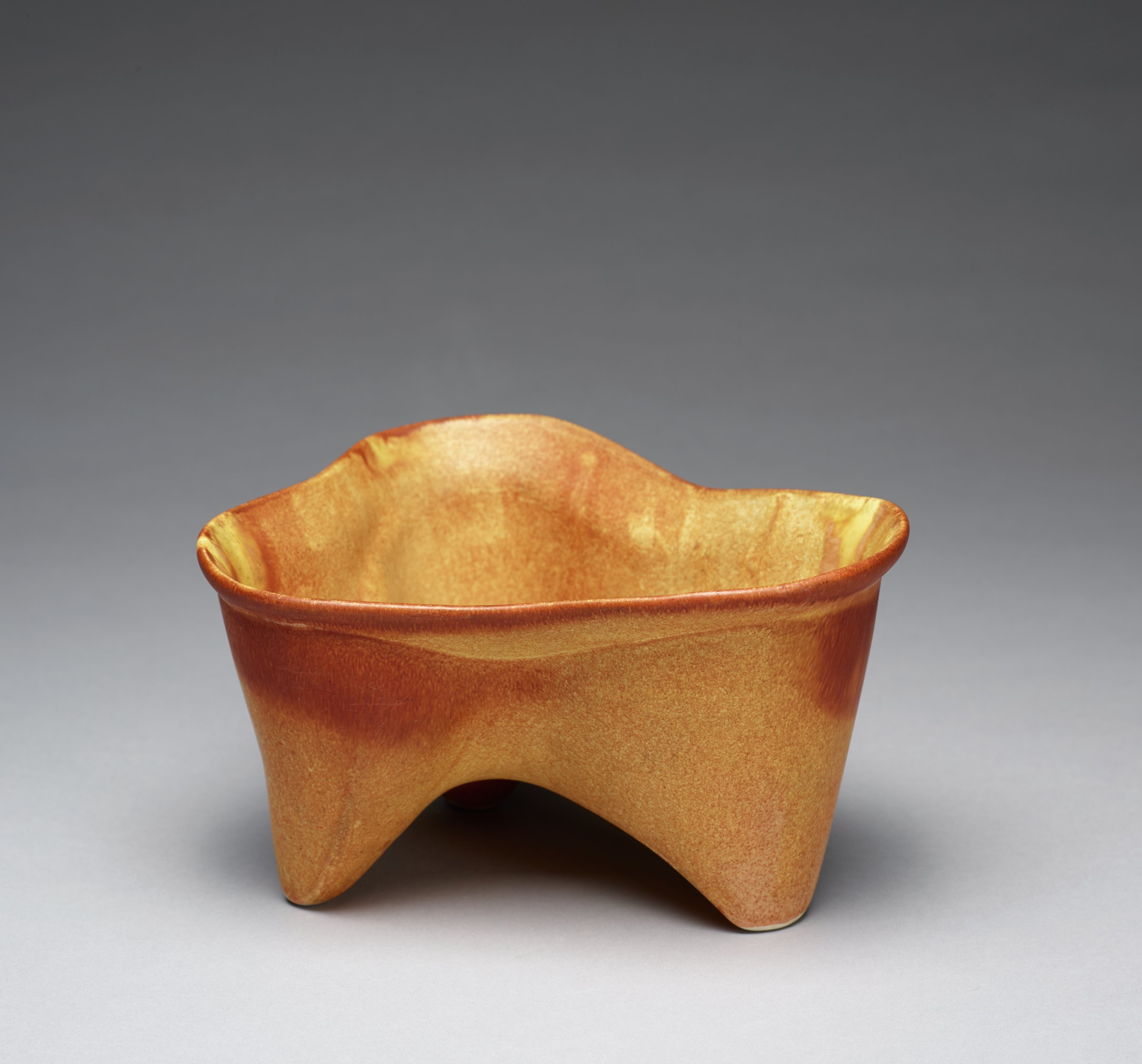 Three-footed molar-shaped vessel with speckled glaze graduating in color from a light tan on the body of the vessel to a darker brown at the rim.