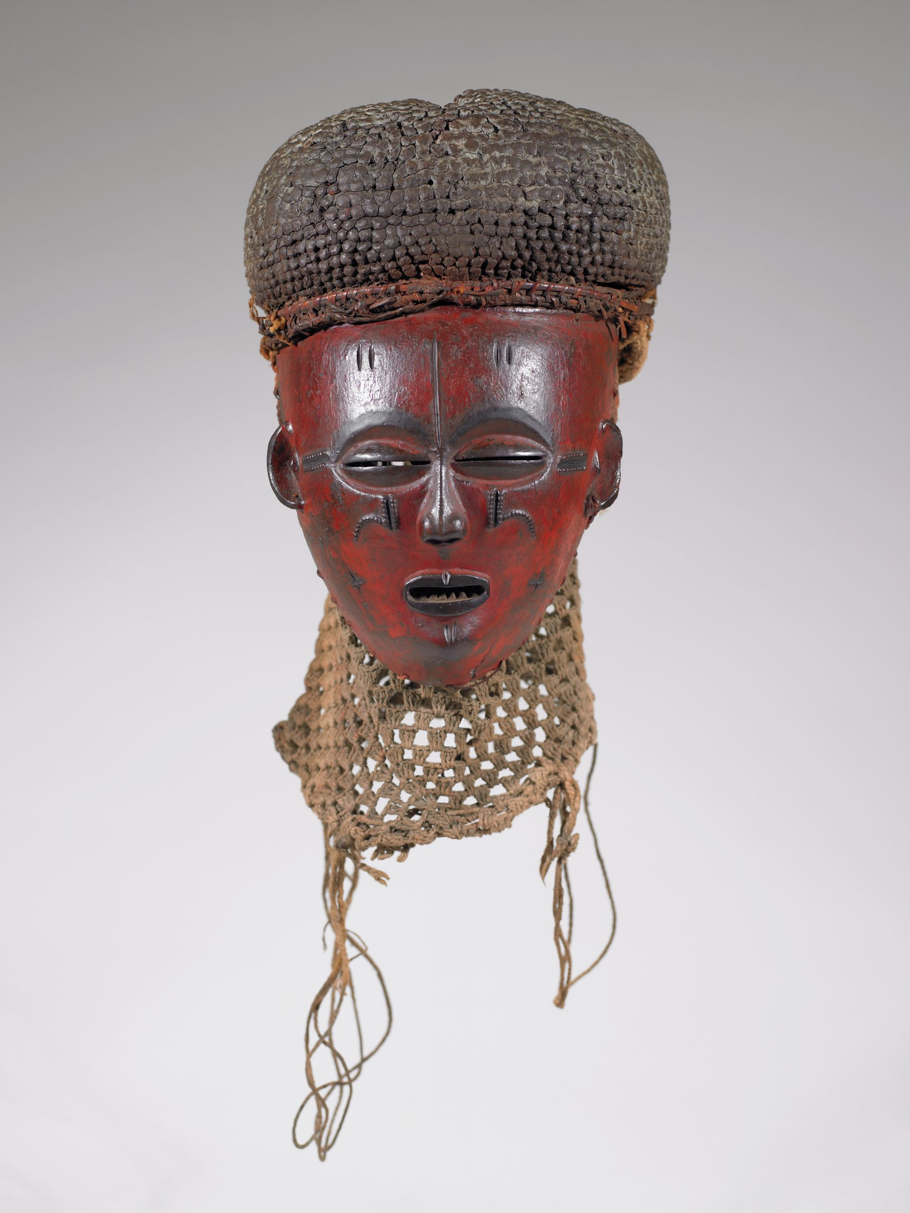 Carved wooden mask with mud packed fiber wig and woven neck piece. Mask used in initiation ritual.