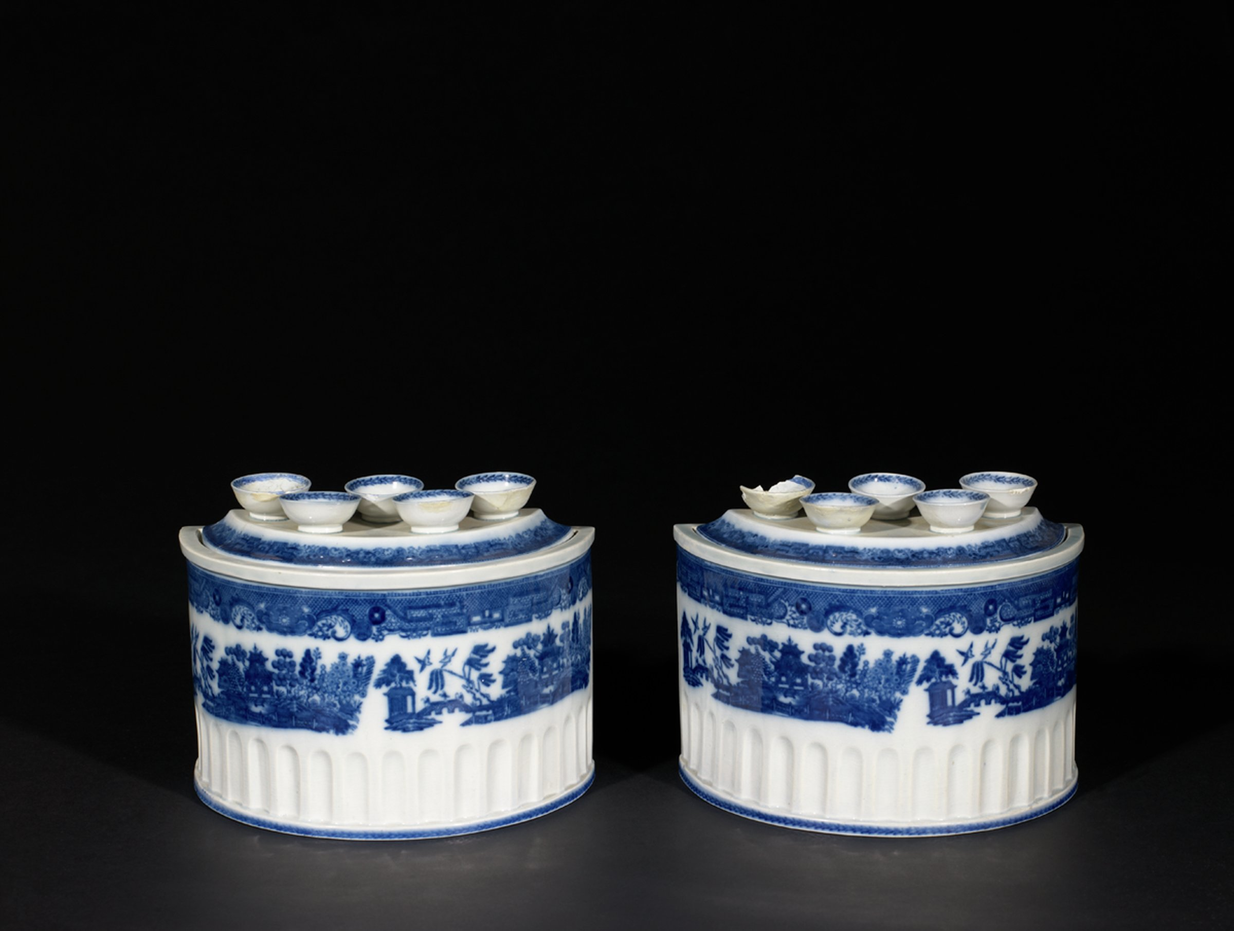 Pair of porcelain bulb pots of demilune shape with fluted lower body and printed cobalt blue decoration of a landscape scene with temples, exotic foliage and birds below a band of scrolls and crosshatching, the conforming cover similarly decorated with five bulb holders each highlighted with a cobalt blue band.