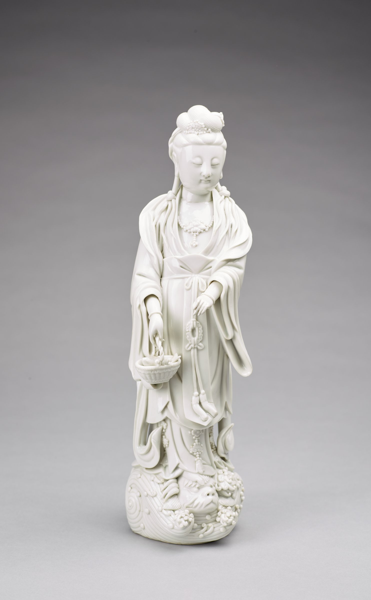Standing figure of Guanyin on waves, holding a basket with a fish.