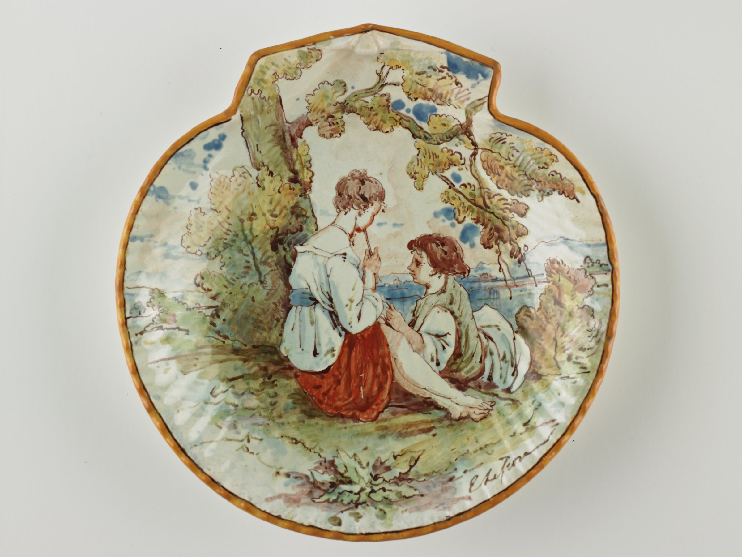 Small, shell-shaped plate with mustard colored edge, in the center the scene of a man and a woman sitting under a tree in a landscape near a water's edge and surrounded by lush flora.  The woman is seated with her knees up wearing a white blouse with blue sash and a red skirt, she plays a recorder while the man leans against her legs, he wears a white tunic and green vest; with blue cloud-like smudges in the sky.