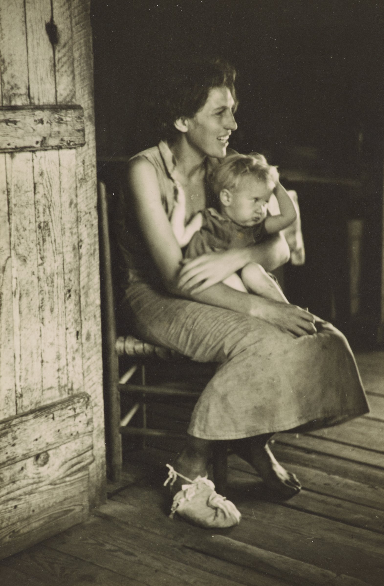 In this black and white photograph, a woman sits to the right of a door, holding a young, blonde child in her arms. The child holds her head and curls her legs on the woman's lap. The woman has dark hair and is wearing a sleeveless dress and one shoe. She is smiling broadly. The black and white photograph is adhered to a buff mount.