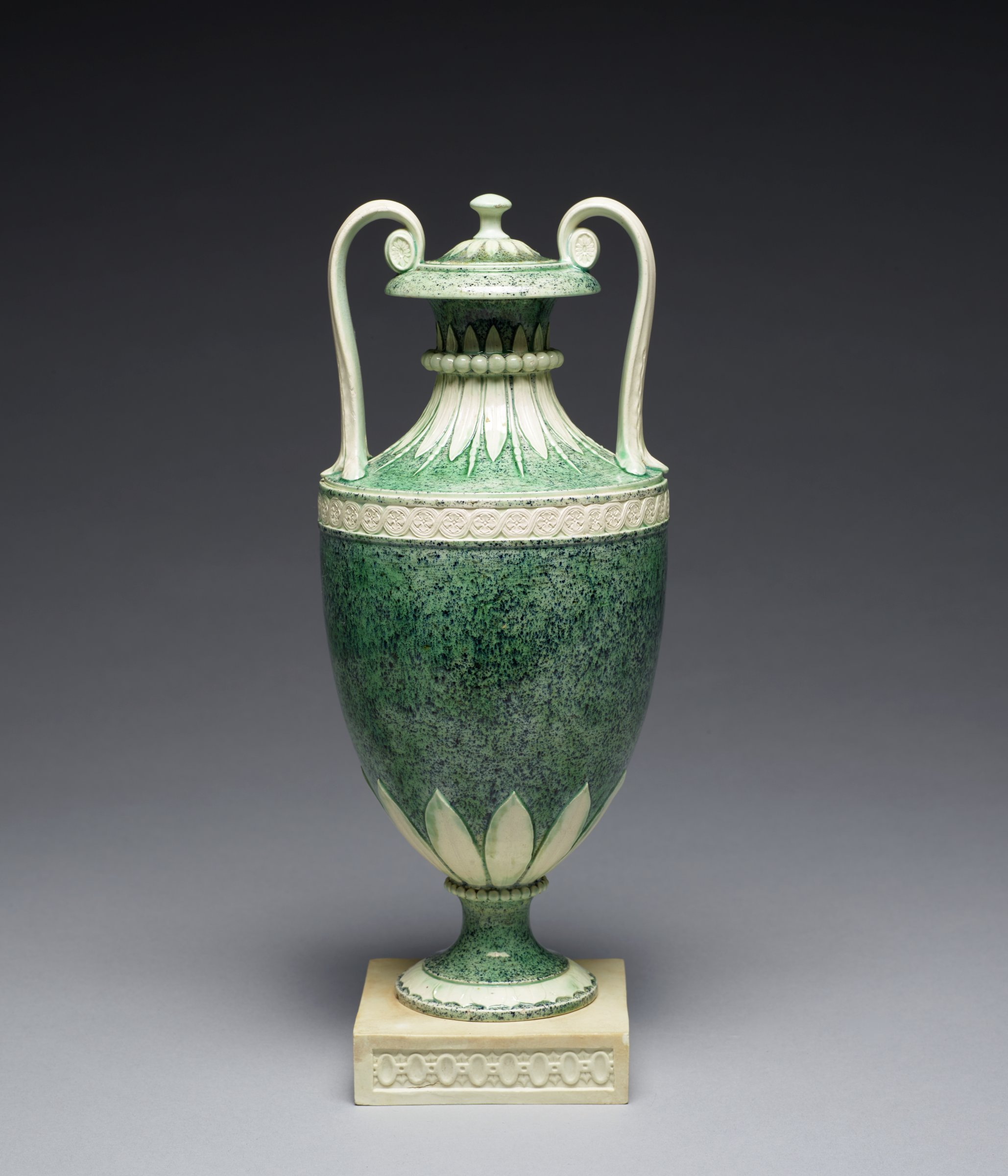 Tall, urn-shaped vase of white stoneware covered with a green variegated glaze and resting on a small, square white stoneware plinth with diaper pattern around, the round foot with overlapping leaves and band of beading at the joint, the lower body with a band of stiff leaf motifs, with a wavescroll pattern below the shoulder and two long curved handles, the elongated neck likewise with band of stiff leaf motifs and beading, the cover with band of leaves and mushroom finial.