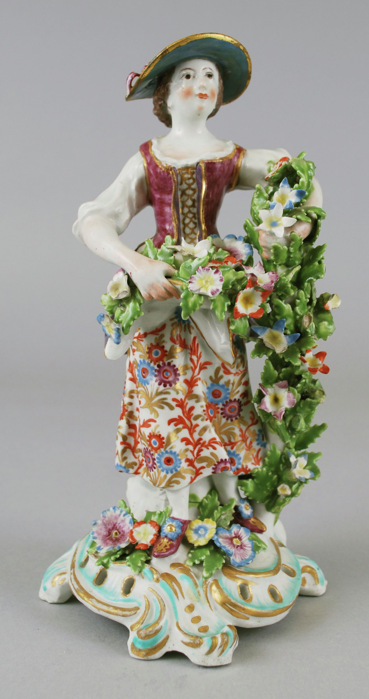 Soft-paste porcelain figure of a woman selling flowers, emblematic of spring, standing in full figure on a rococo base highlighted in gold and green, to her left a flowering branch that offers the figure support, around her waist a white apron filled with bunches of flowers, her left arm encircles the flowering branch, wearing a flowered and striped skirt with purple bustle and puce bodice tied together with gold string over a white blouse, her hat is red and blue.