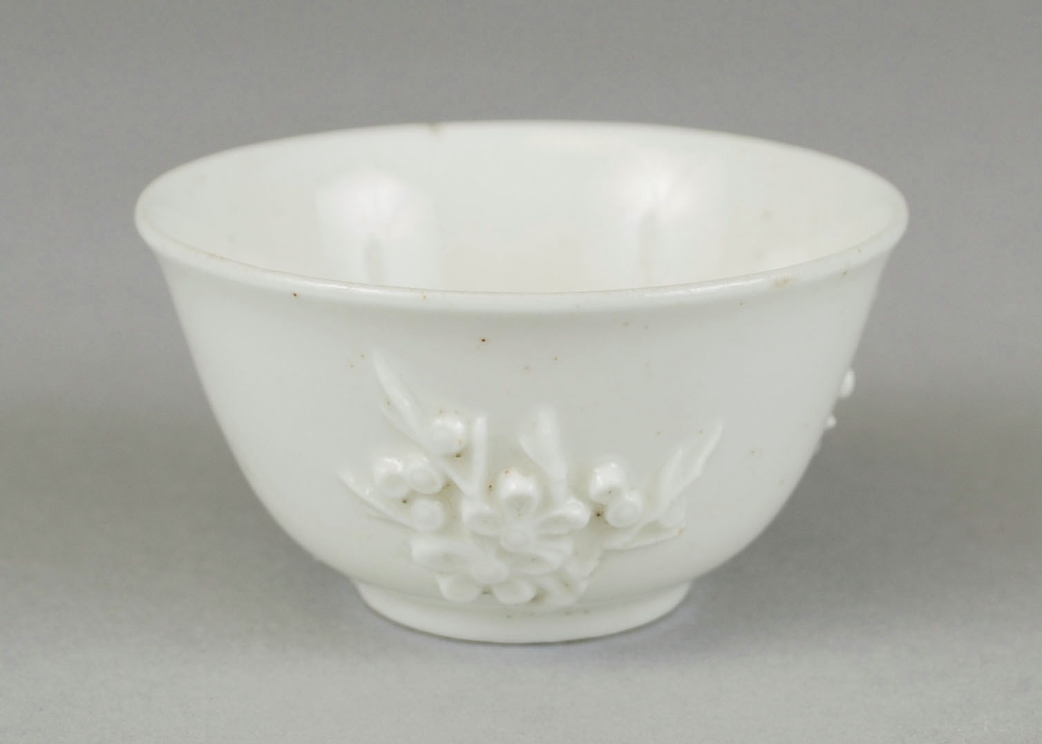 Small white, soft-paste porcelain tea bowl of blanc de chine type with molded prunus decoration on the exterior.