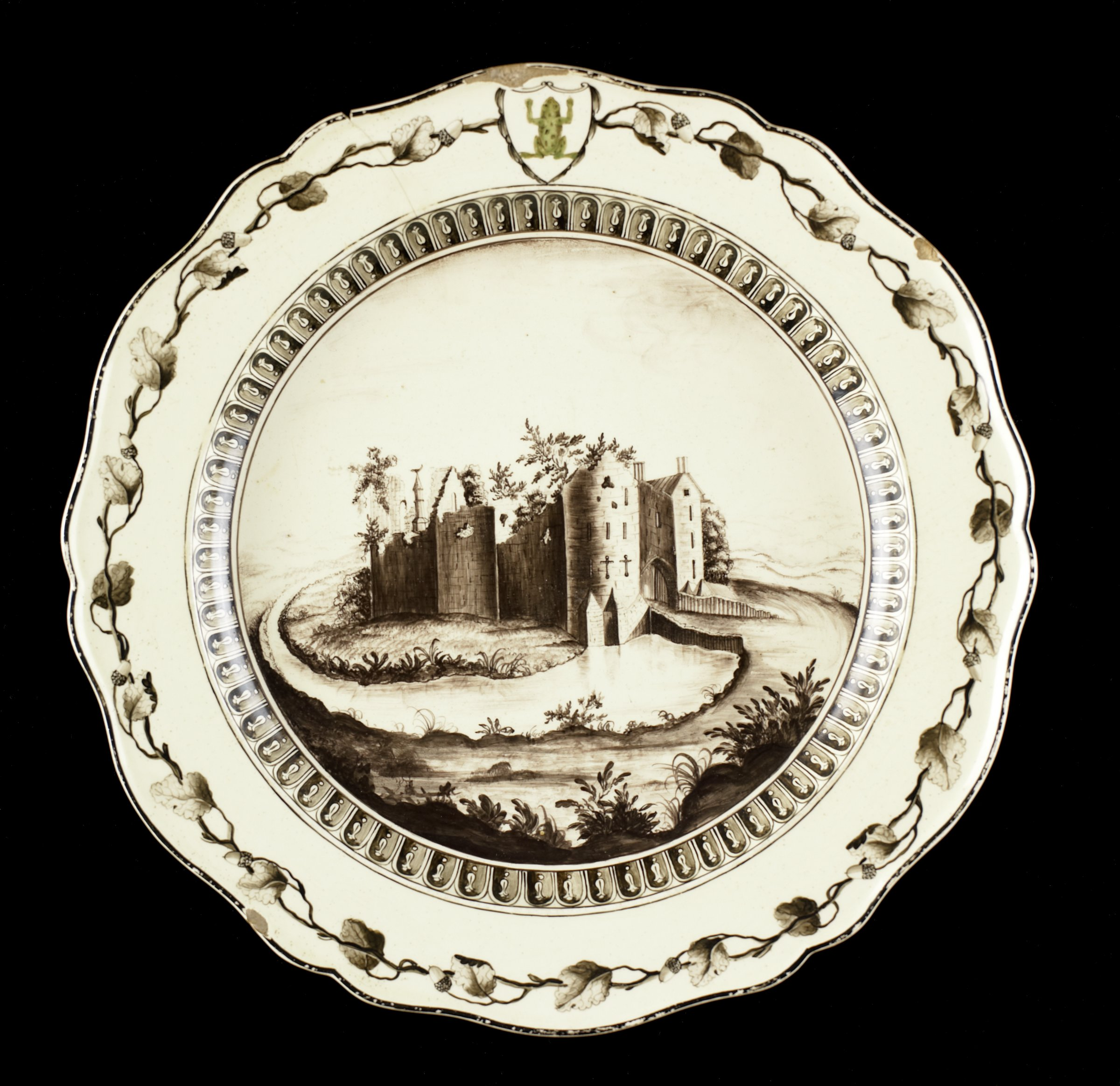Round creamware dinner plate with petal-shaped rim decorated in monochrome sepia enamel with a hand painted scene of St. Briavels Castle in Gloucestershire, England, from the east, within a border of false gadroons, the rim of the plate has a garland of oak leaves and acorns around its perimeter with a central shield-shaped cartouche within which a stylized, green-enameled frog, with a small band of sepia enamel on the edge of the rim.