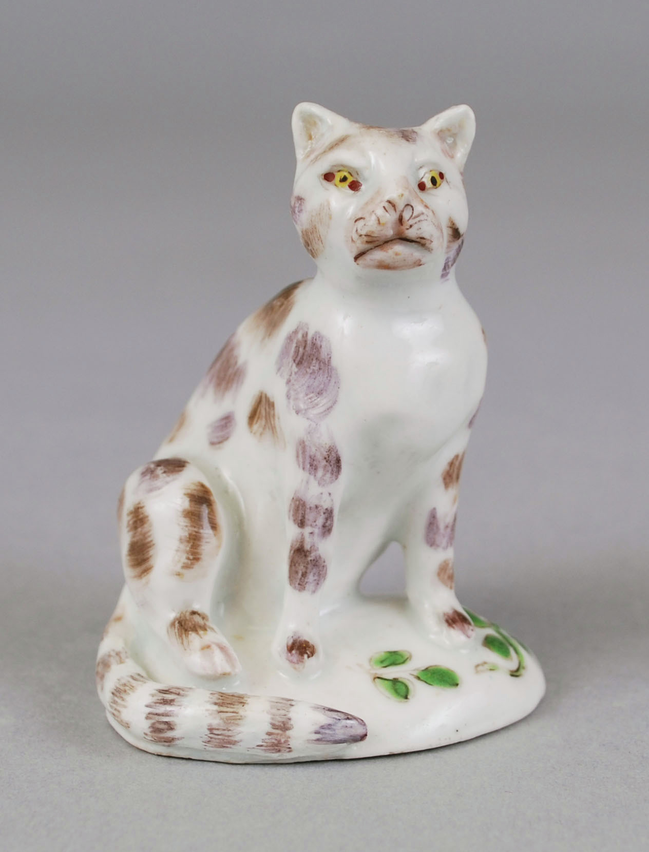 Small seated Bow porcelain cat of white color with brown patches. The eyes are painted yellow and paws have black lines for nails. The tail curves around next to the left of the feet. The cat sits with one foot slightly away from the body, on a circular base with painted flowers and green vines.