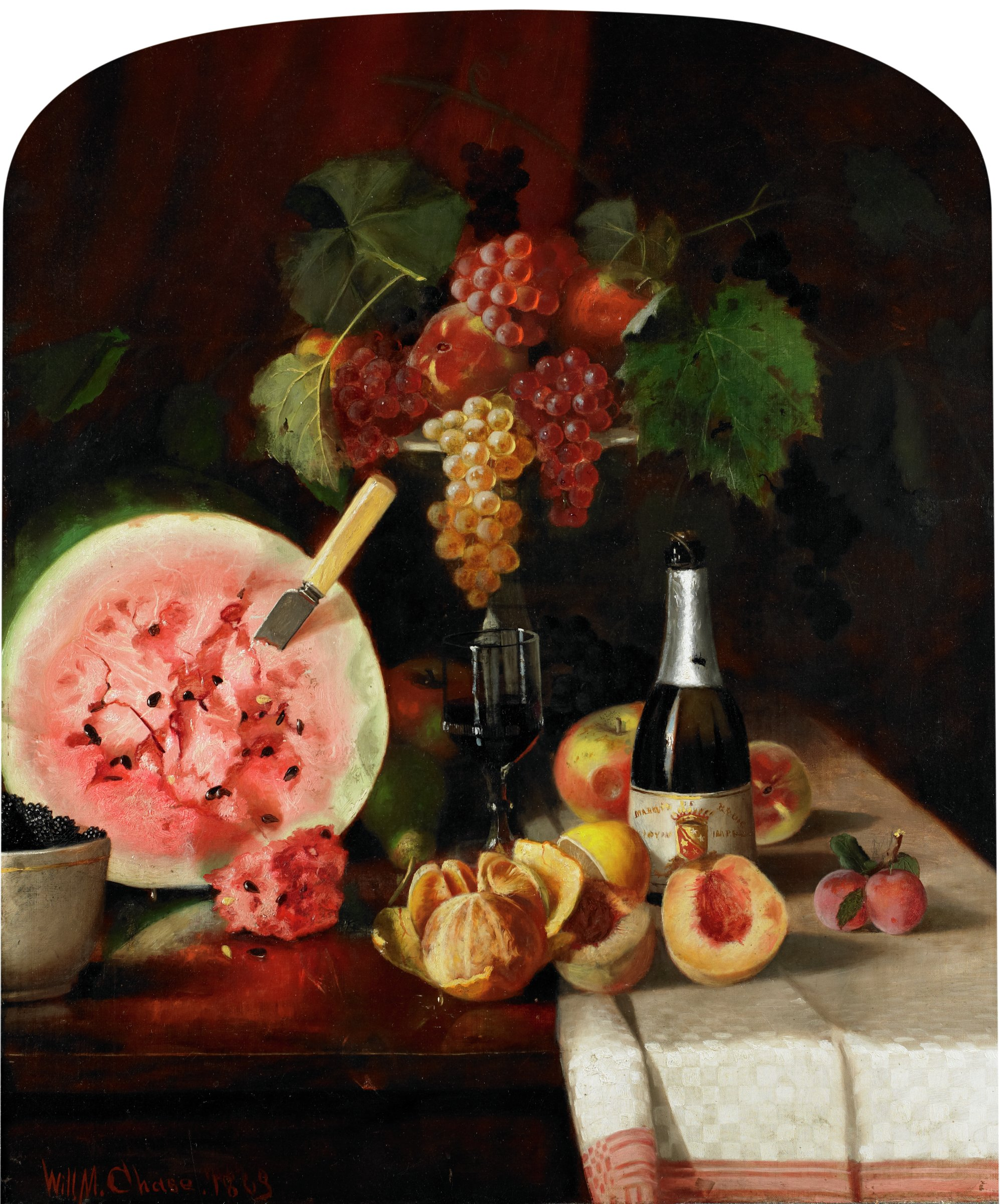 In this still life, fruit and a bottle of wine are situated on a table. From left to right, the composition includes blackberries in a bowl, half of a watermelon with a knife protruding and a piece carved off in front, a partially peeled orange, one half of a halved lemon, both halves of a halved peach, and a bunch of plums with stems and leaves still attached. Behind the halved peach is the bottle of wine, and behind the bottle of wine are two apples. To the left of the bottle of wine is a partially filled wine glass, and behind the glass is a pedestal holding apples and bunches of grapes. The painting is on a dark background. The right of the table is covered in a red and white table cloth.