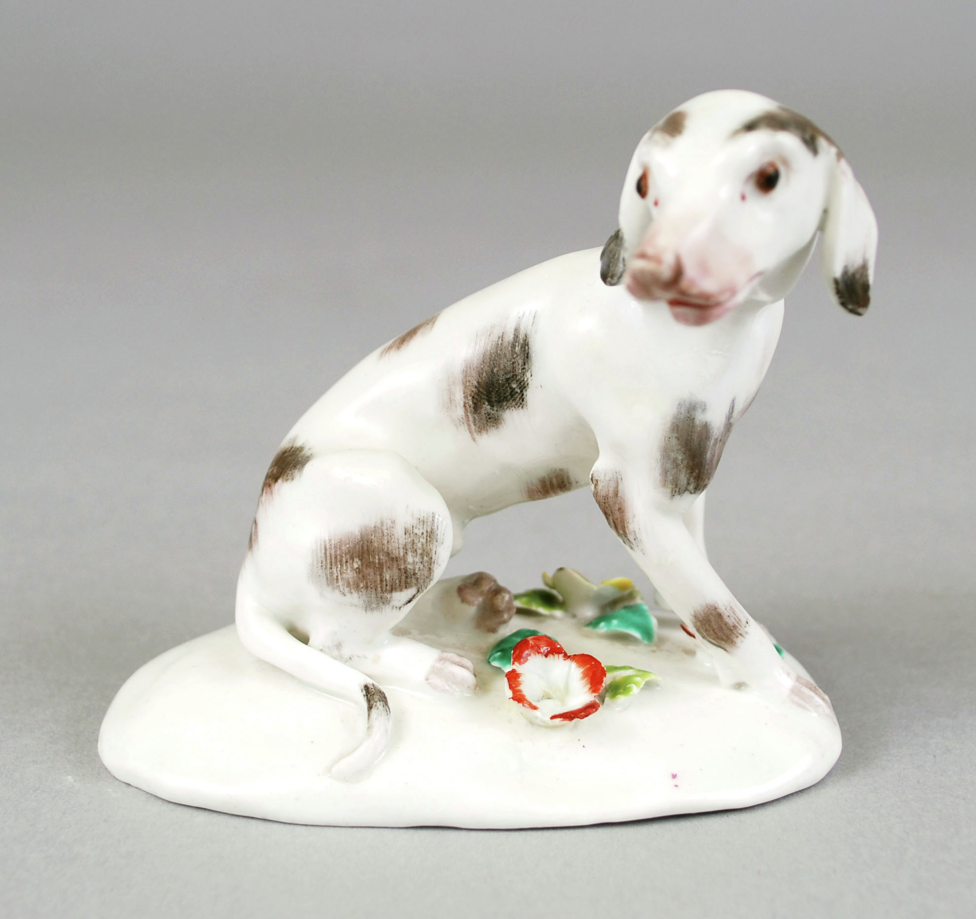 A small Bow Dismal Hound seated on its haunches with head turned and tail curved to the left. The dog's white coat is colored in patches of brown. The dog figure is seated on an oval shaped base decorated with three flowers of red, yellow and rust colors with green leaves.