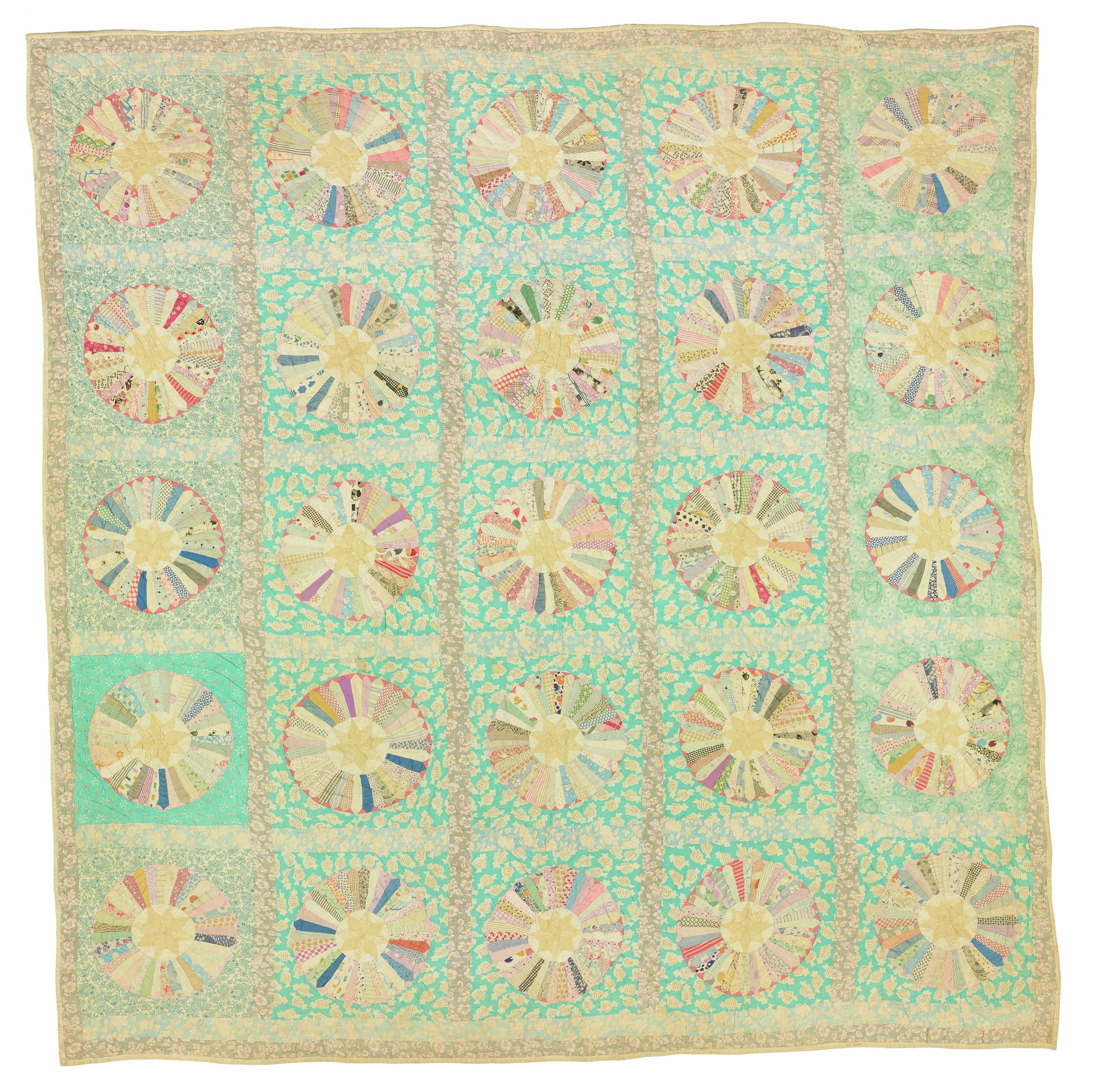 Large, square quilt made of cotton feed sacks in the form of a grid of 25 blocks, the ground fabric of each block in shades of green, the central blocks with the image of candy in wrappers, the two outer rows of green floral prints, the fourth block down in the far left outer row of a darker green-ground fabric, in the center of each block is a colorful wheel comprised of a series of radiating arms or rays stemming from a central medallion with a small yellow star in the middle, the grid and border defined by a floral fabric in a different beige-green shade.
