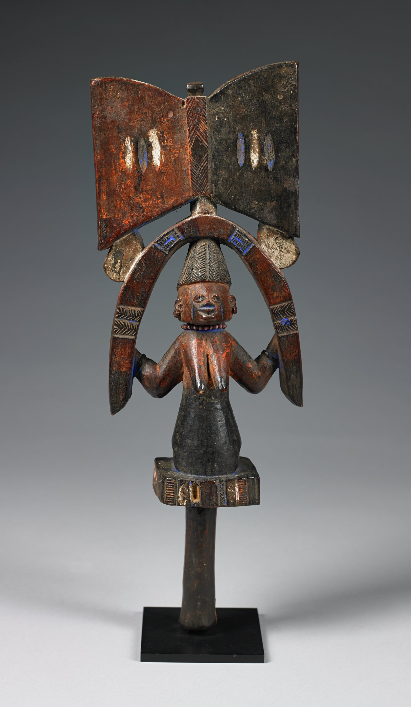 Staff surmounted by the double axe motif, stylized reference to the thunderbolt believed to be hurled from the skies by Shango, with kneeling female figure.