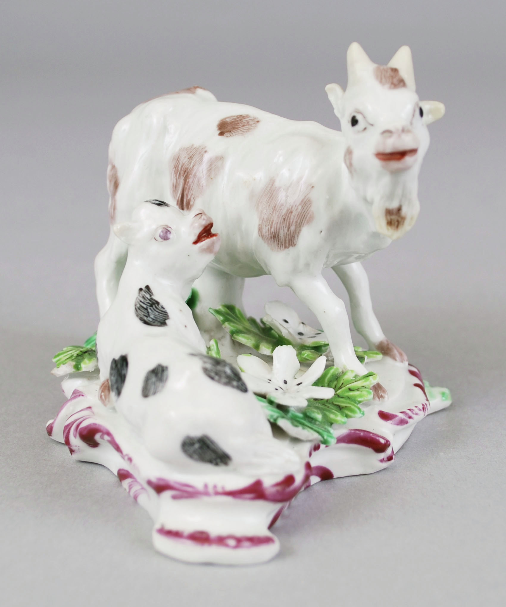 Bow porcelain goat and kid facing each other. The goat has brown patches and is standing while the kid painted with dark gray patches in sitting. The scroll base is painted in burgundy strokes and decorated with green foliage and white flowers.