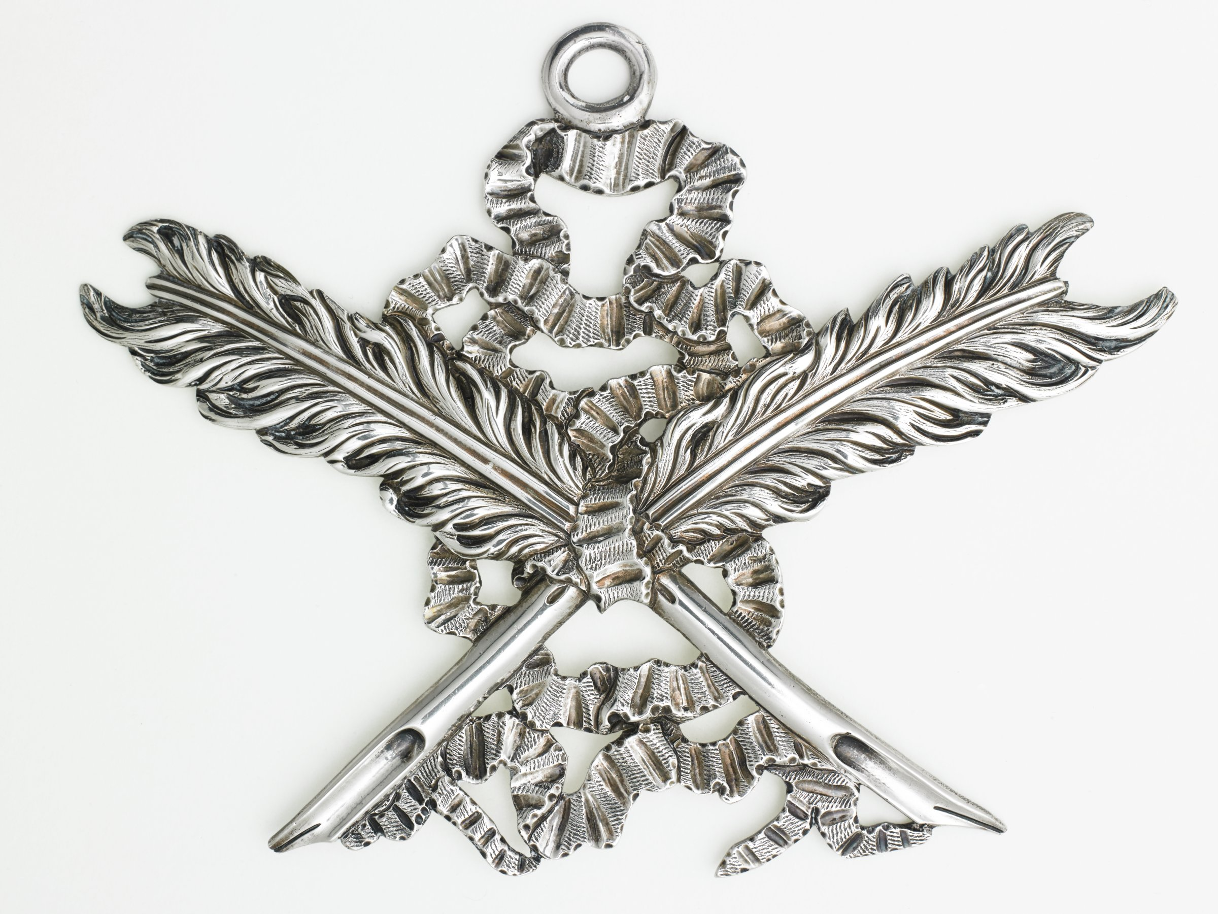 Large silver pendant, or jewel, made for the secretary of a Masonic group, in the form of two crossed feather quills with a ribbon, at the top a large eye through which to thread a chain from which to hang the jewel.