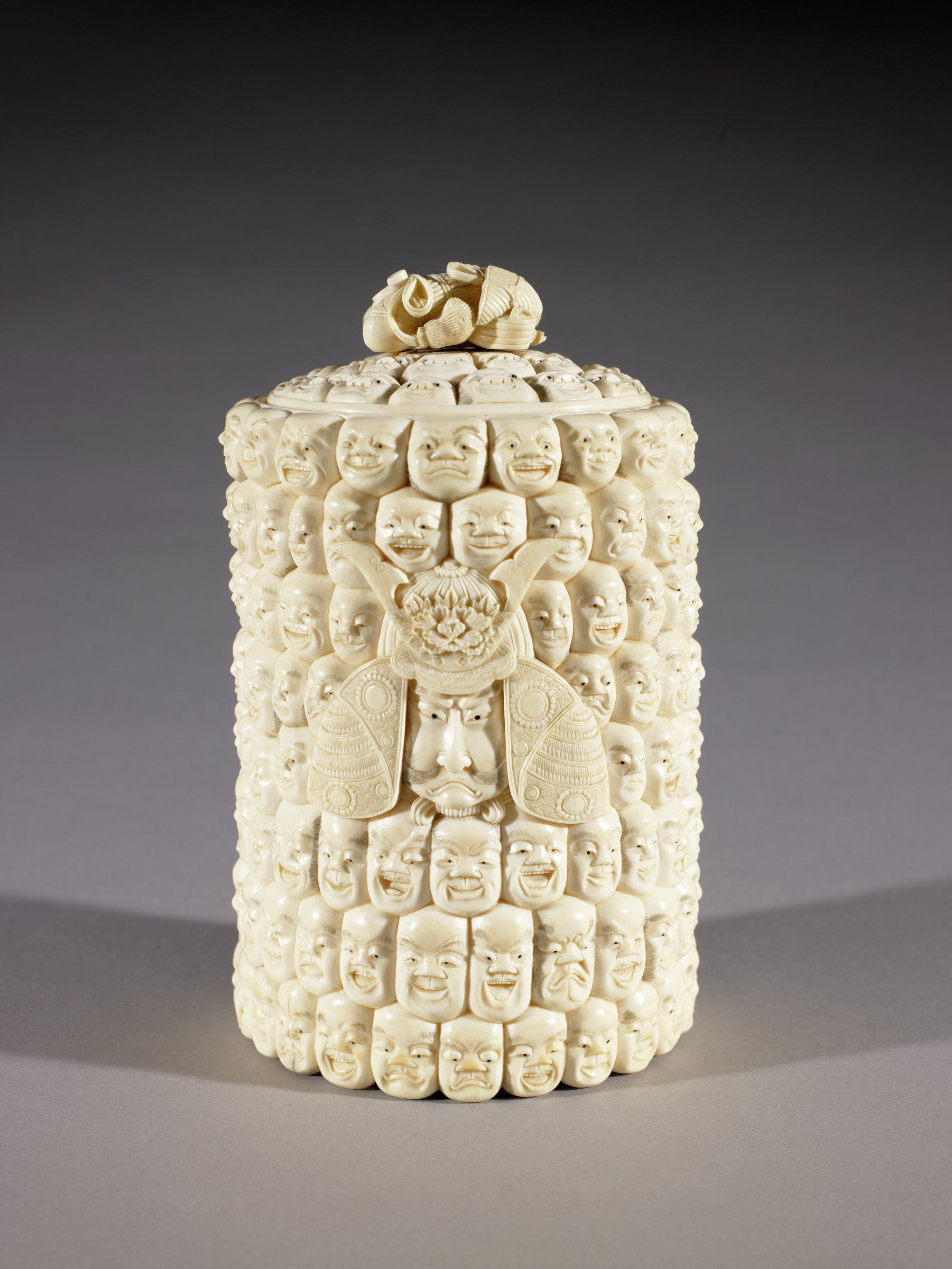 Lidded Box carved from an ivory tusk with one hundred faces featuring one larger dominant head wearing a helmet (Kabuto)