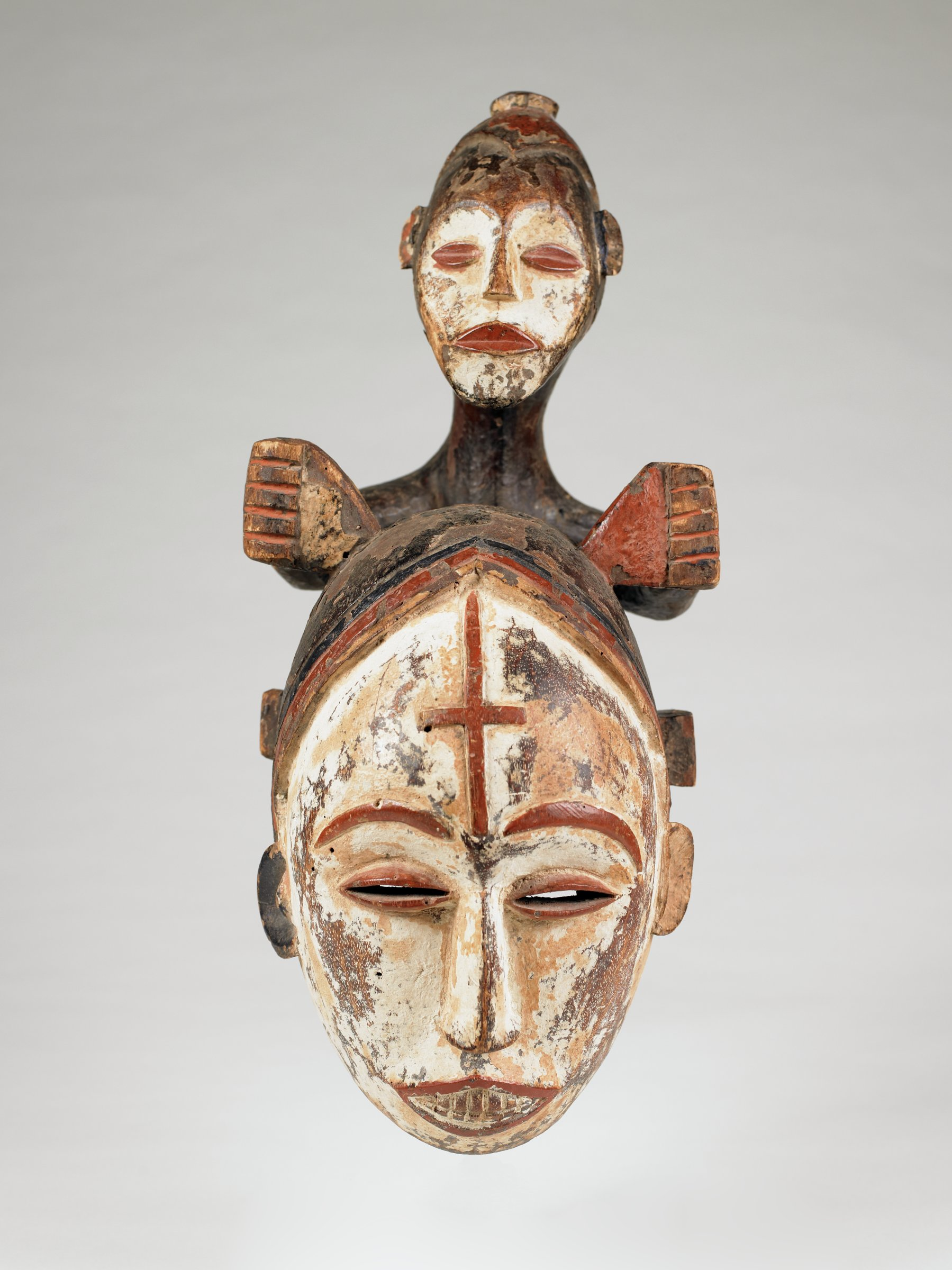 White-faced helmet mask of woman's face and head, surmounted by child figure