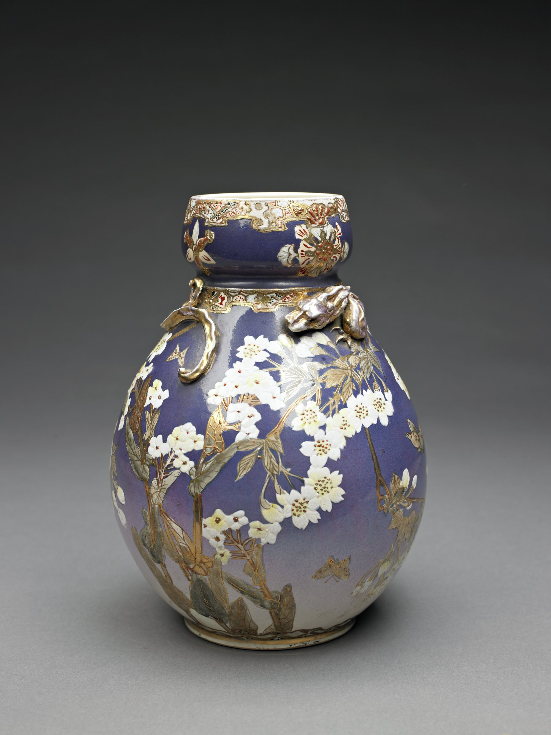 A double-gourd shaped vase. Upper and lower portion with a background of blue/purple that fades out at base of vase. Painted with five branches with yellow flowers (unidentified flower) and six butterflies in a spring setting. Raised gold decoration on veins of leaves, stamens of flowers and wings of butterflies. Upper portion decorated with four chevron floral designs equally spaced on blue ground. A dentated floral band around lip and around shoulder where spheres join. A worn, gilded dragon crawls in and out of the surface of the vase and the top of the first sphere. Cream-colored glaze on interior and on foot. Four character mark on foot.