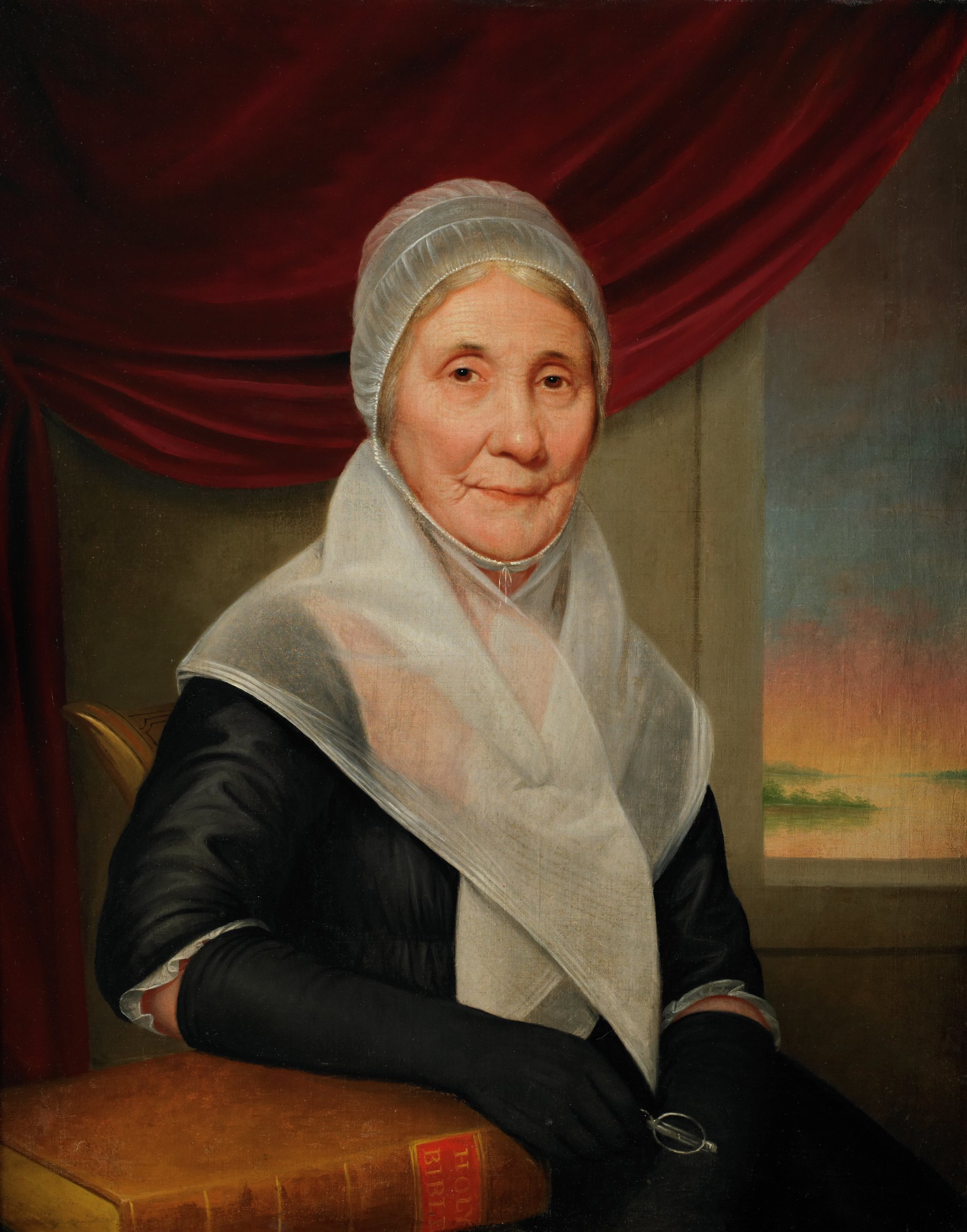 Three-quarter-length portrait of an elderly woman seated in a painted chair (the chair's ear is visible at far left) before a wall with a red curtain drawn to reveal a window, at right, through which can be seen a sunset painted in peach pink hues. The woman—who gazes directly at the viewer—wears a black dress with white trimmed sleeves, full-length black gloves, and a diaphanous white linen cap and kerchief. Her right arm rests on a large family Bible. She hold holds a pair of spectacles in her right hand, suggesting that she has just been reading the Scripture.