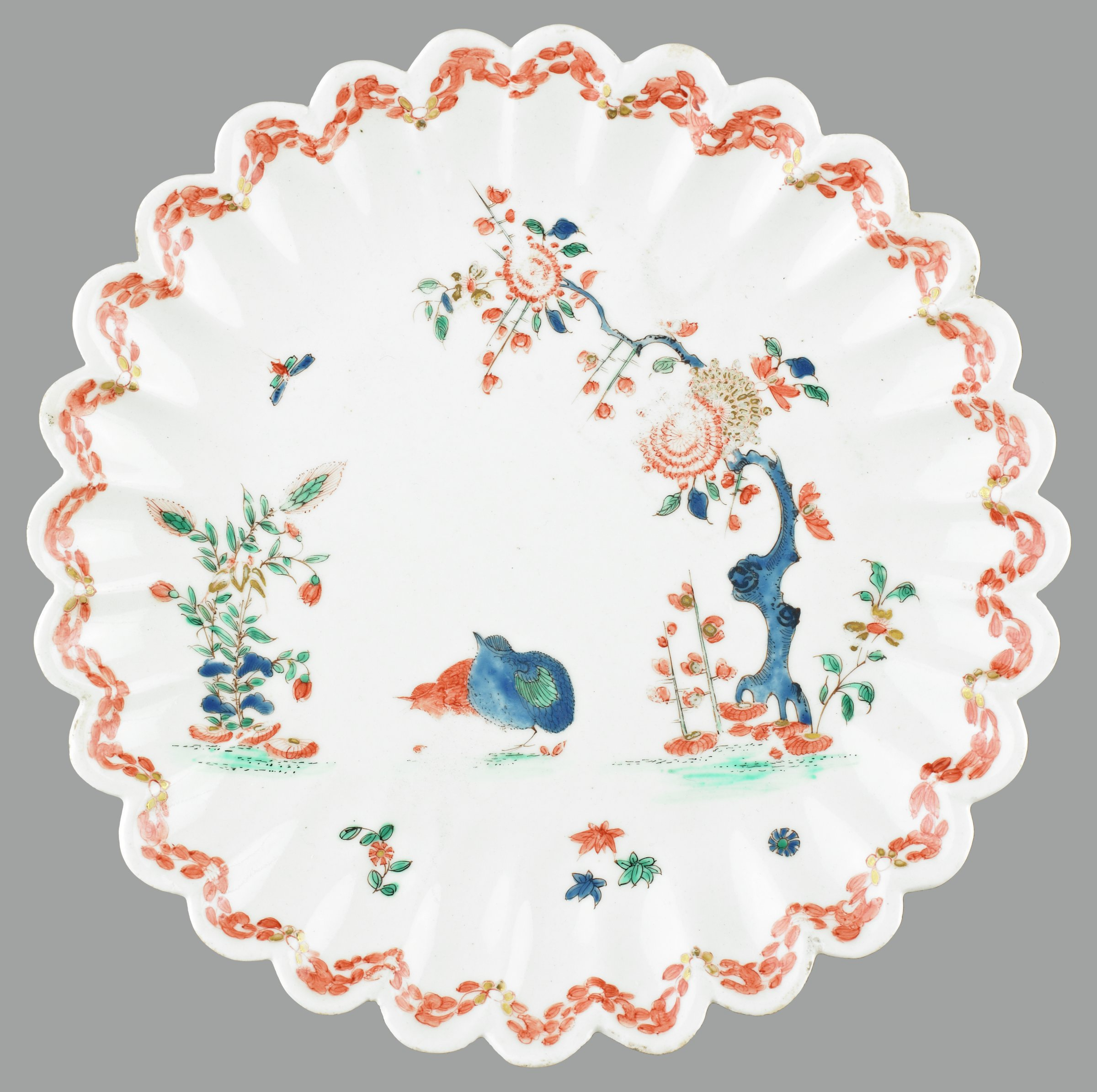 """Plate of white soft-paste porcelain with scalloped edges decorated with the Kakiemon """"Two Quail"""" pattern depicting a scene of two quails, one painted in iron red, and the other in blue with green tipped wing feathers, pecking at seeds beneath an arched prunus tree with blue painted trunk and iron-red and gilt decorated flowers in bloom, and facing a flowering shrub with large leaves, the edge with an iron-red meandering leaf border."""