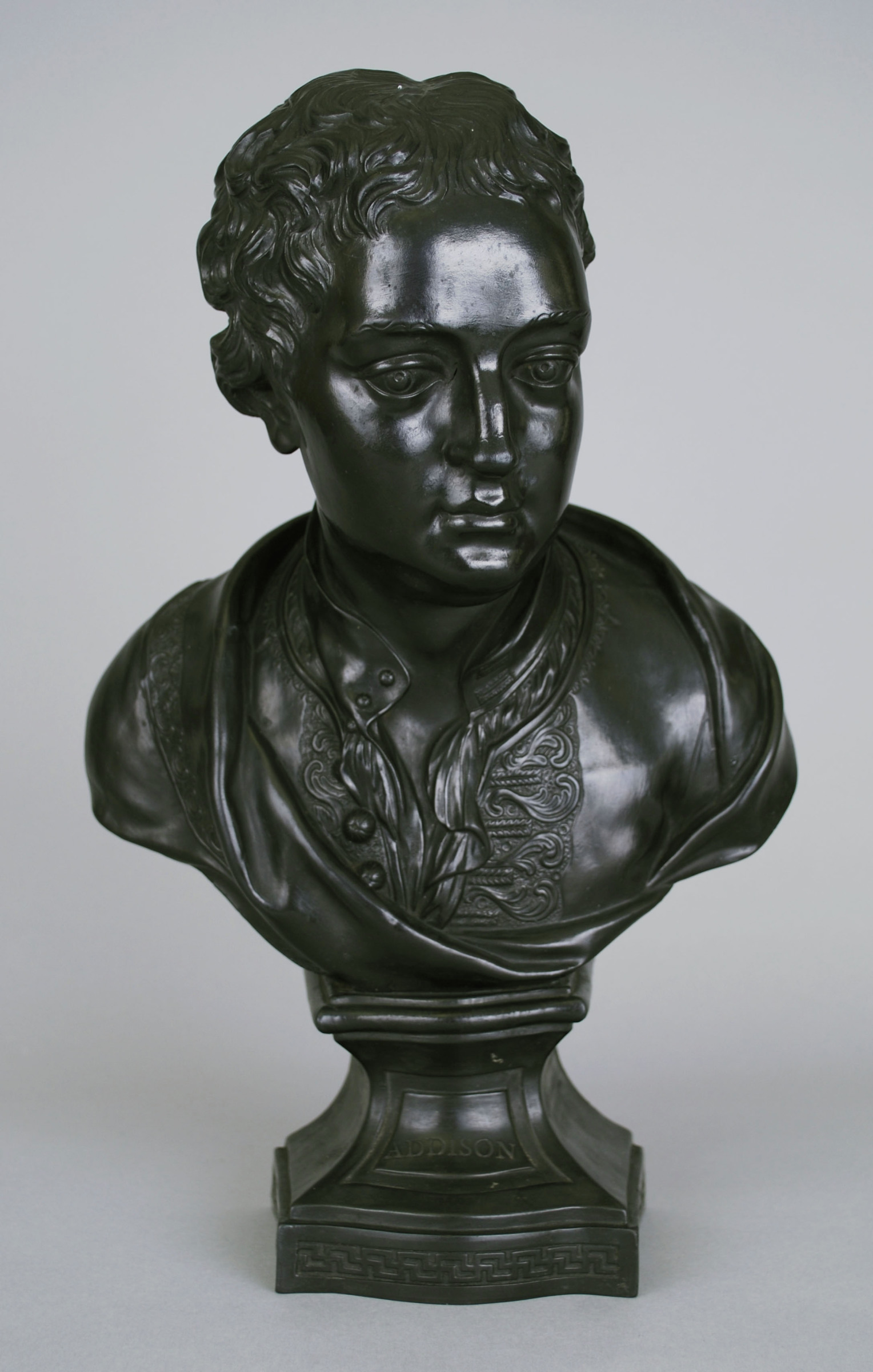 Bust of the English poet, playwright and politician Joseph Addison (1672-1719) in black basalt made in one mold with hollow body and flat back, the socle square with bombay front and small reserve in which the name ADDISON and with a Greek key border along the lower edge, Addison depicted with short hair in civilian dress with loose shirt with open collar and embroidered jacket, with drapery that features embroidered trim.