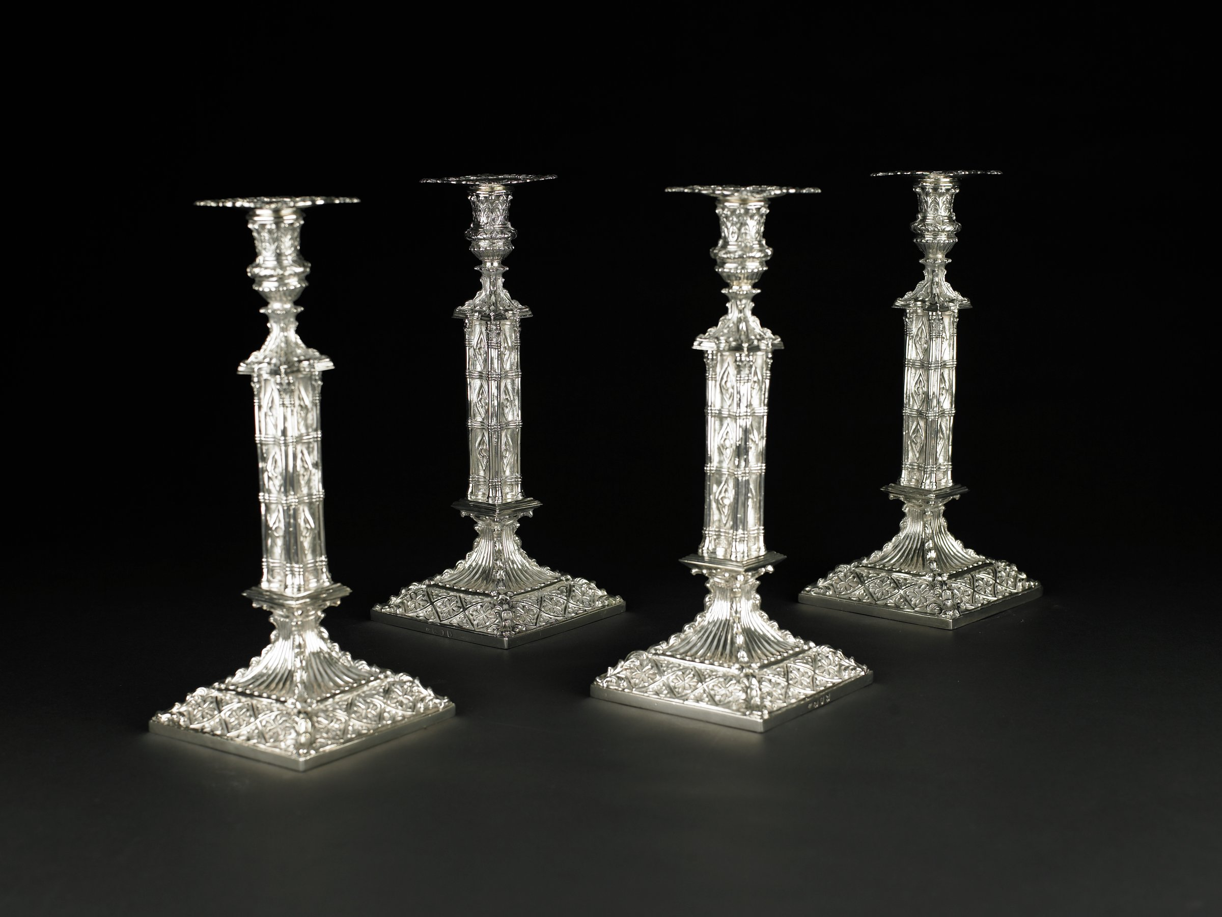 Set of four, tall, sterling silver candlesticks architectural in form and neo-Gothic/neoclassical in style, each with a large, square base decorated with a diaper pattern within which are stylized flowers raised against a stippled ground, the corners are covered with upwardly scrolling acanthus leaves; from the base the stick rests on a fluted foot upon which sits a square pedestal from which extends the actual stick, which is composed of two slender columns at each edge with acanthus leaves at top, all bound by three sets of three bands each; between the columns are quatrefoils; the finial is in the form of a footed urn, the foot with four individual trefoils between acanthus leaves, the urn is also decorated with trefoils and stylized acanthus leaves, and holds a square, removable bobeche with pierced corners and scrollwork; on three of the four bobeches is an engraved crest: an eagle with outstretched wings atop a crown set with feathers.