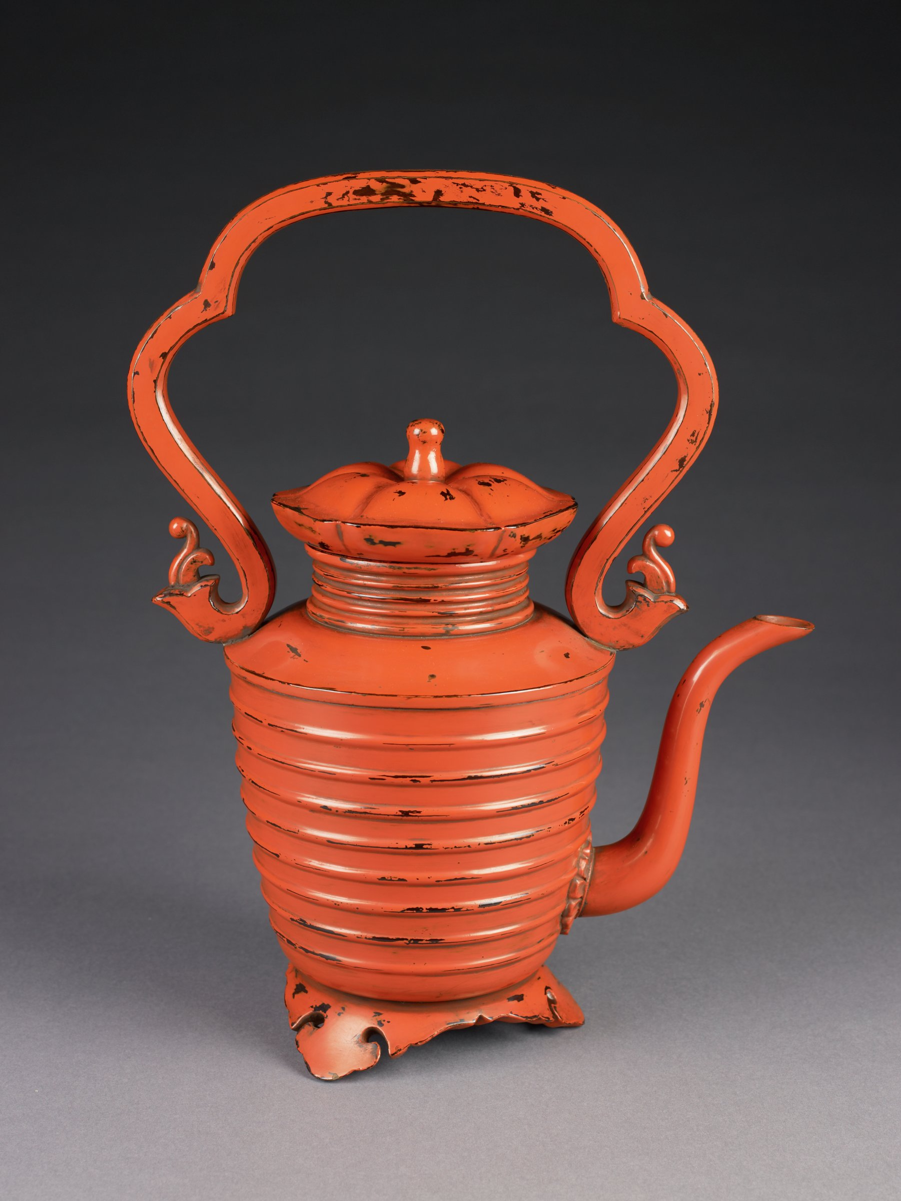 The hot-water ewer, supported by three cloud-collar feet, is covered by red lacquer with an undercoating of black lacquer.  Both the body and the neck are decorated with raised bands. The piece displays both a sense of sturdiness and gracefulness in shapes seen in Negoro ware. The large sweeping handle with stylized floral fittings and the swan-neck spout reveal the elegant design of the piece. The black lacquer underneath revealed as a result of the wear of the red lacquer is part of the aesthetics of modern Japanese folk art.