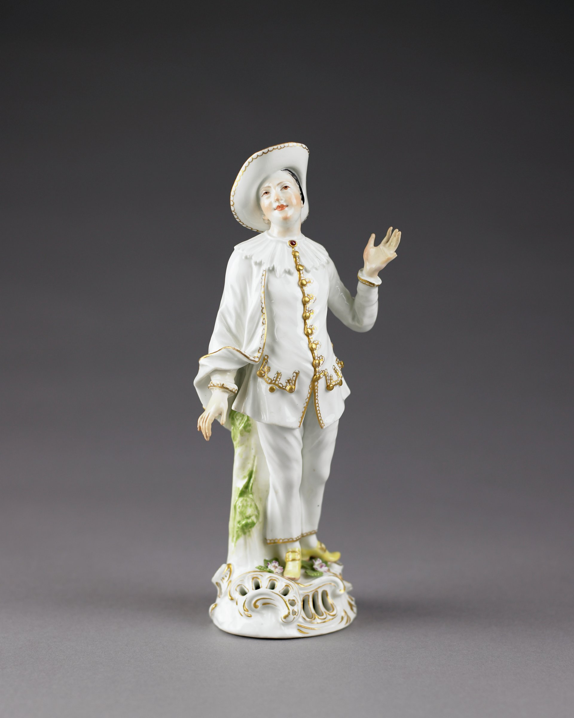 The figure of Pierrot standing on a rocaille base with pierced and gilded scrolls, the base decorated with small applied flowers in lilac with green leaves, Pierrot wears a costume in white consisting of trousers and a jacket trimmed in gold, with a ruffle collar, and a large hat with the brim rolled up on the left side, his left hand is raised, palm up and open, the right arm is lowered at his side, the shoes are yellow with gilt buckles